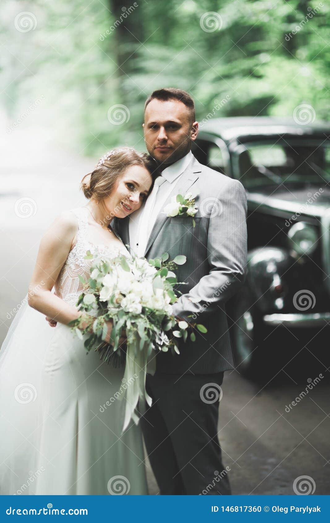 Giovani coppie romantiche felici caucasiche che celebrano il loro matrimonio esterno