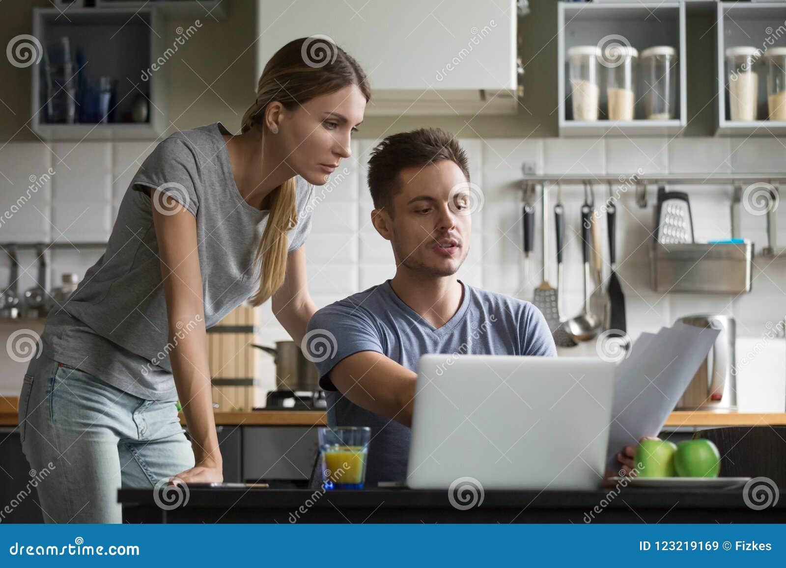 Giovani coppie serie che discutono le fatture domestiche con le carte e la l