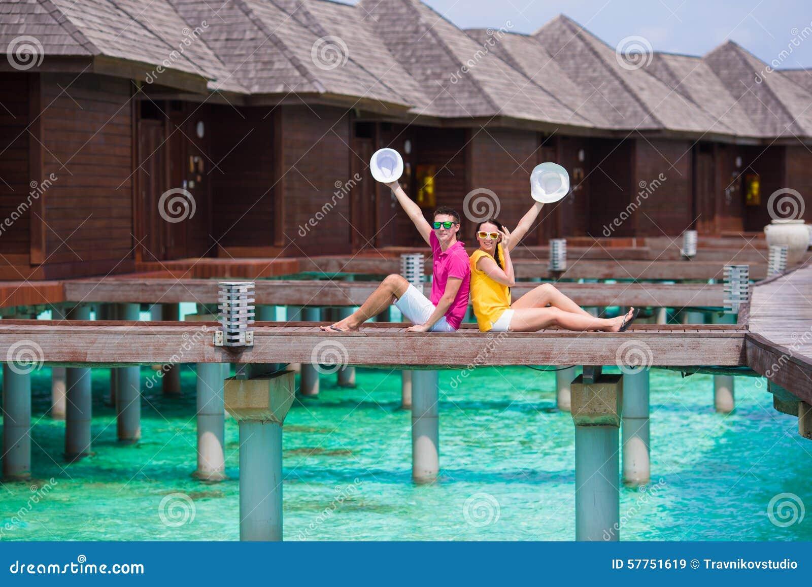 Giovani coppie sul molo della spiaggia vicino alla villa - Alla colorazione della spiaggia ...