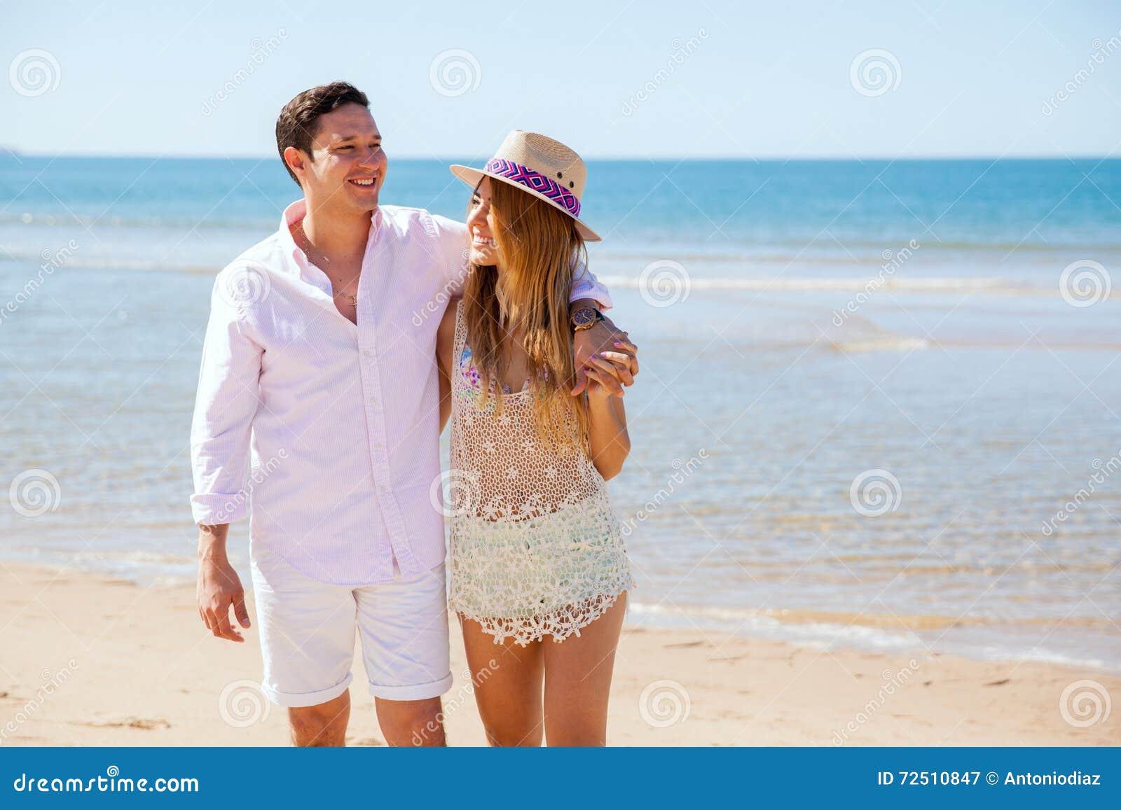 Giovani coppie sveglie che camminano dalla spiaggia