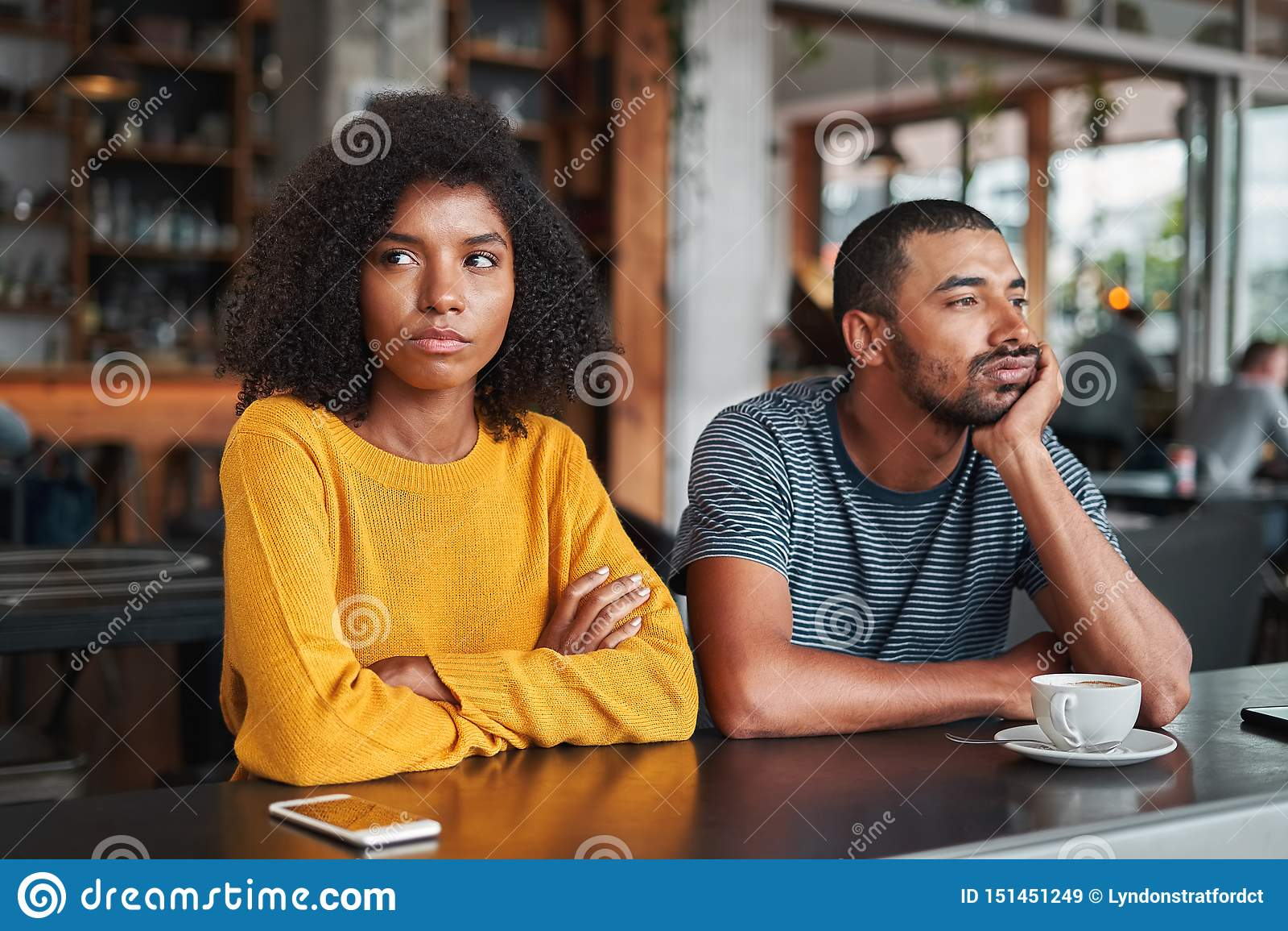 Giovani coppie tristi ed arrabbiate in caffè