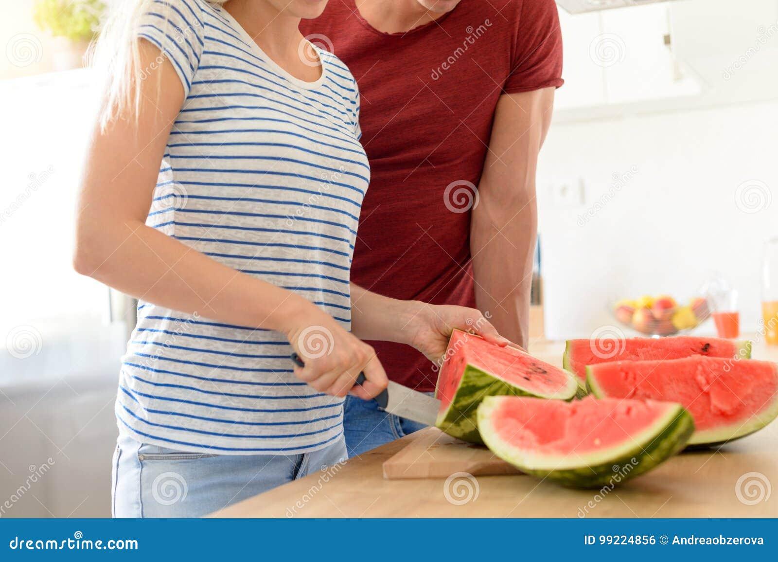 Giovani coppie in una cucina che affetta anguria rossa Coppie nella loro cucina bianca contemporanea