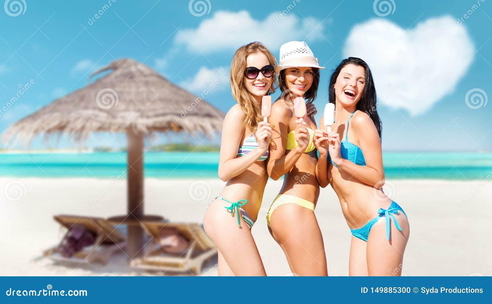 Giovani donne in bikini con il gelato sulla spiaggia