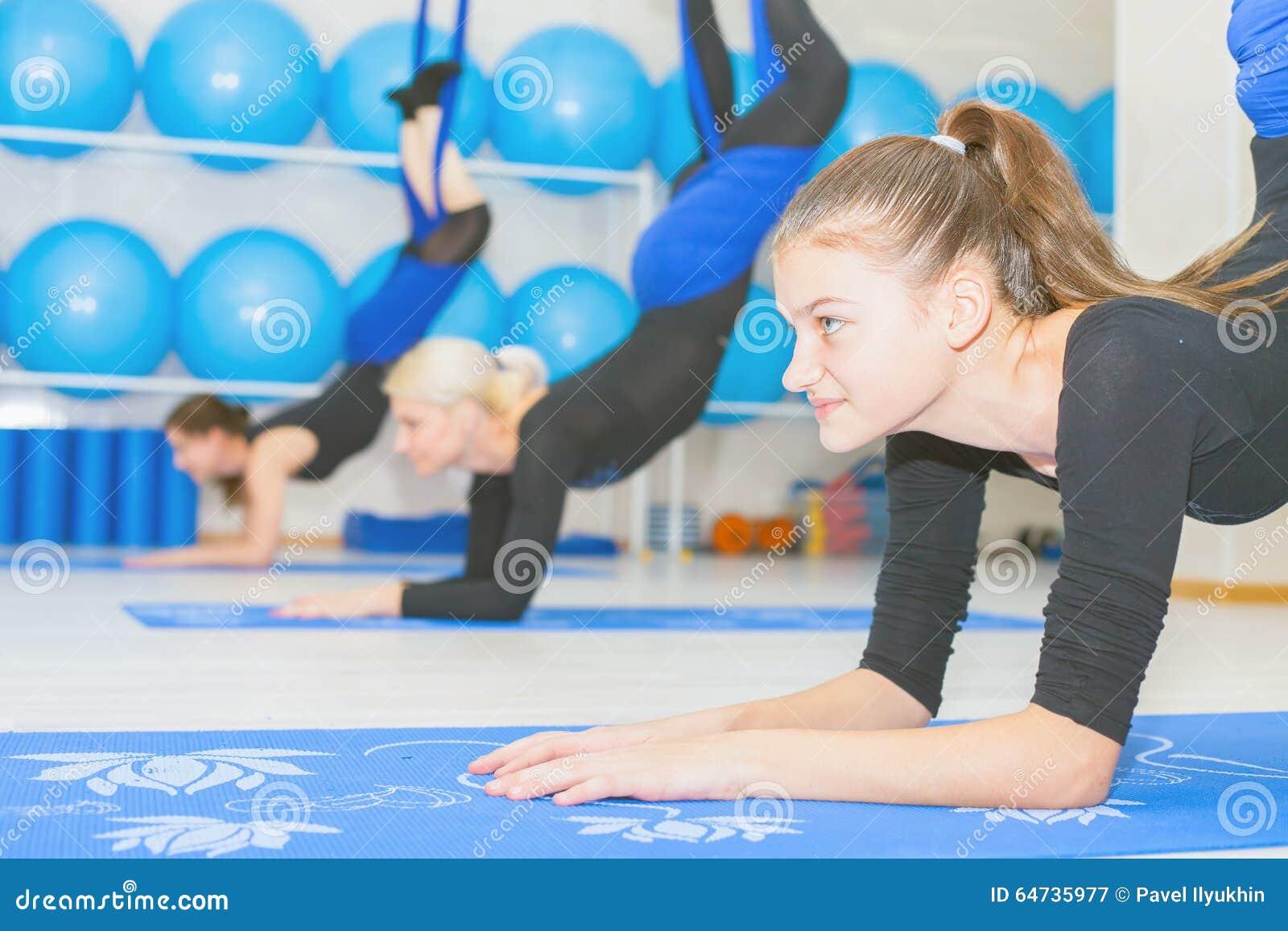 Giovani donne che fanno esercizio aereo di yoga o yoga antigravità