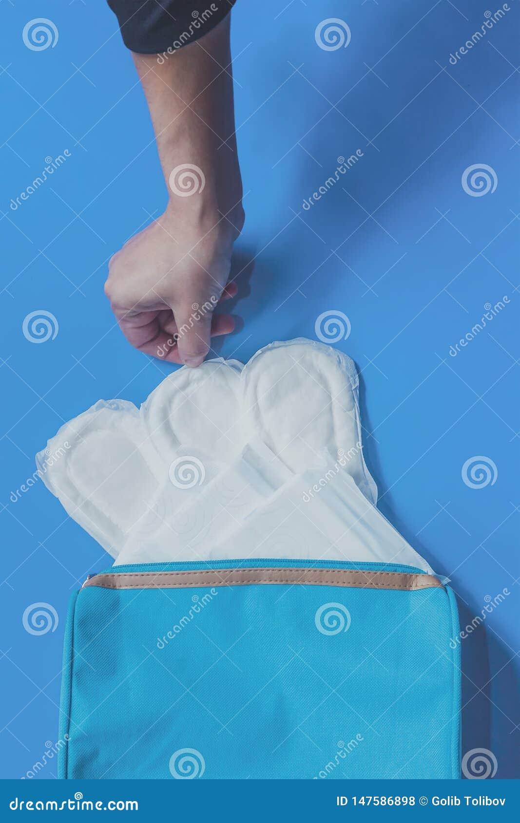 Giovani donne che prendono i cuscinetti sanitari dentro della sua borsa cosmetica su fondo blu