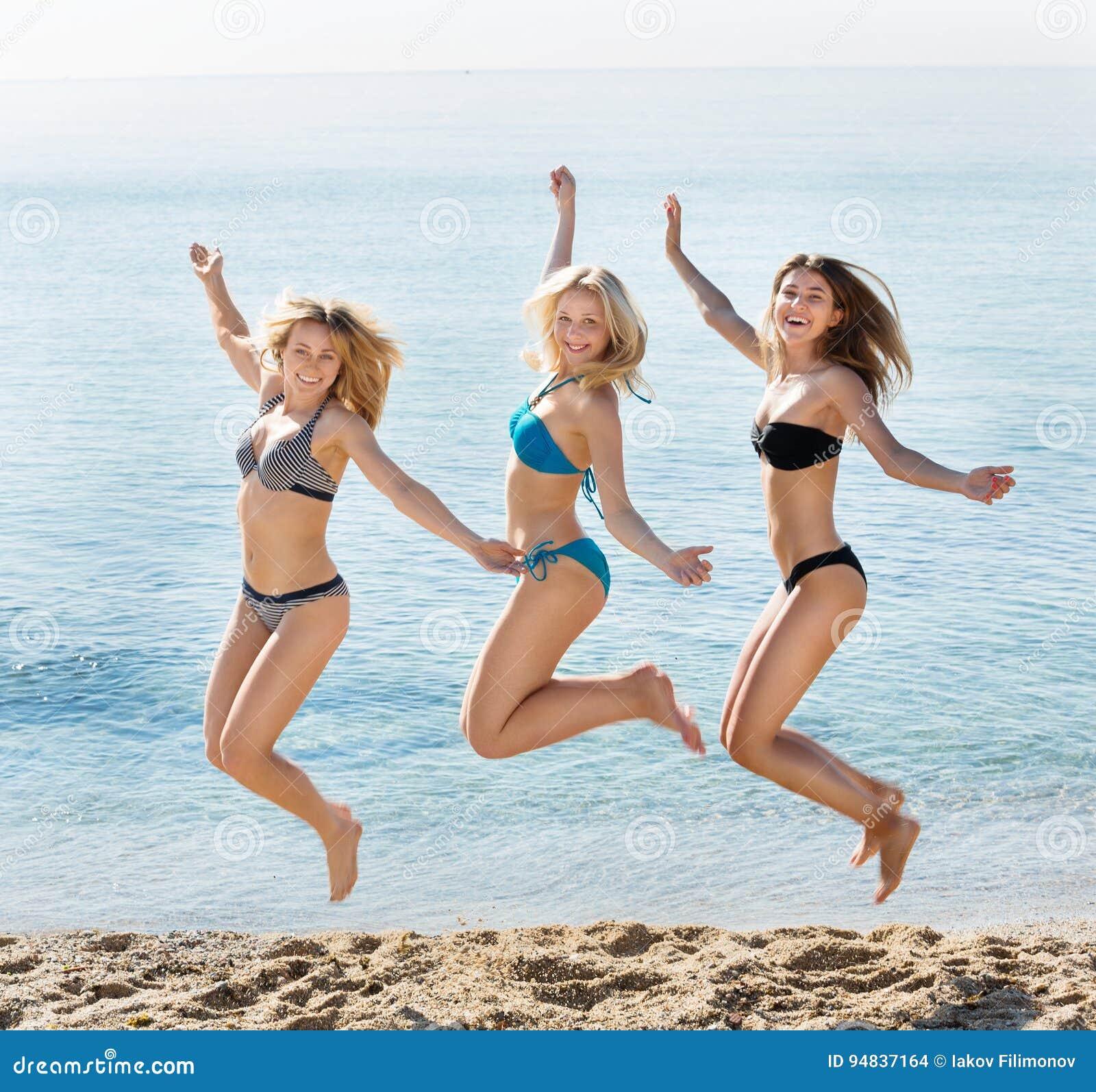 4d2c330d9938 Un ritratto di tre giovani donne allegre in costumi da bagno che saltano  insieme sulla spiaggia Fuoco sulla persona centrale