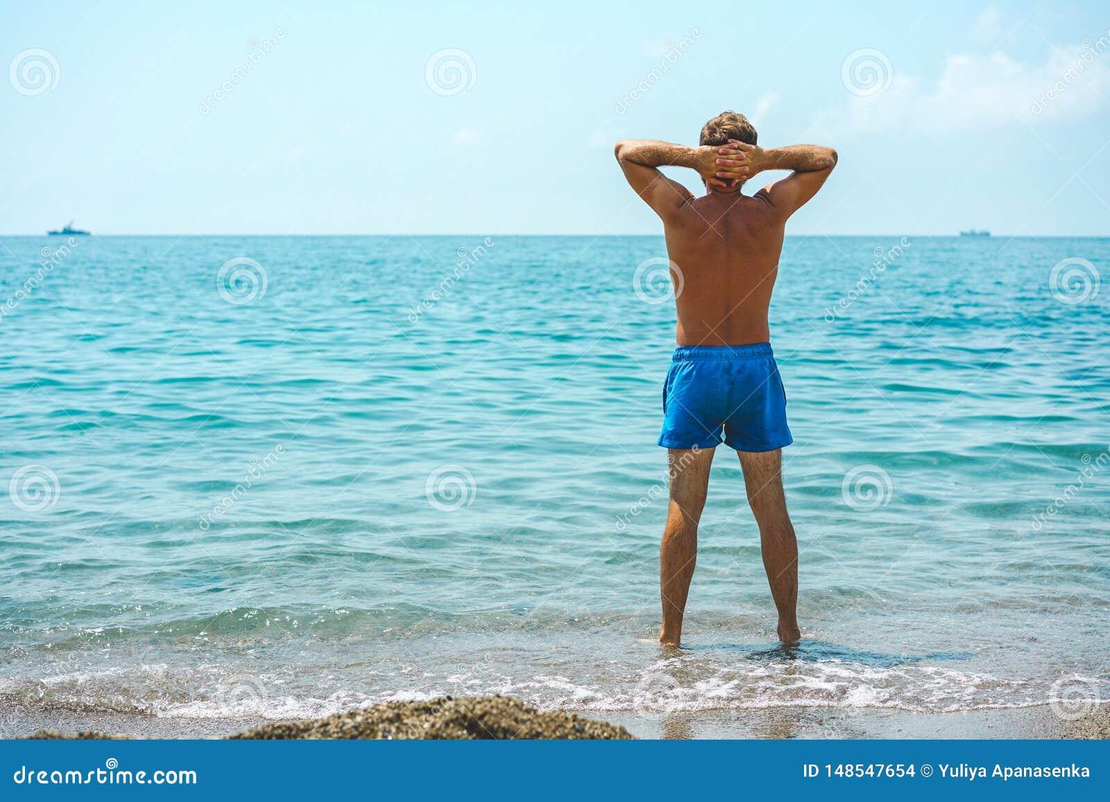 Giovani ed uomo in costume da bagno che sta sulla spiaggia e che esamina il mare