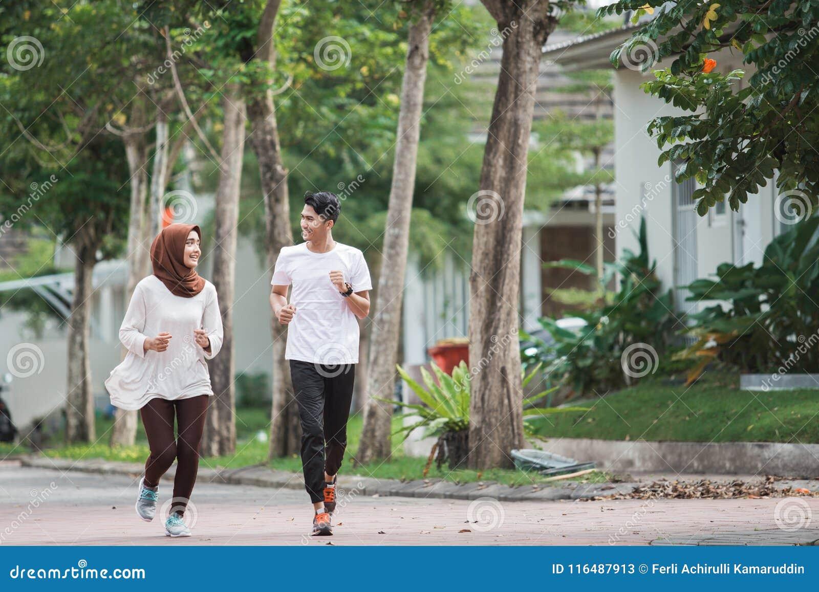 Giovani esercizio e riscaldamento asiatici felici delle coppie