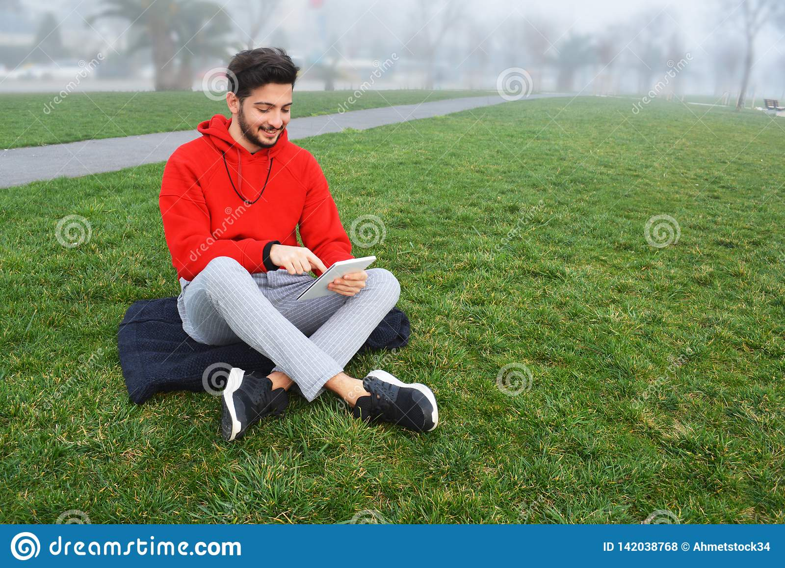 Giovani facendo uso della compressa digitale in parco pubblico