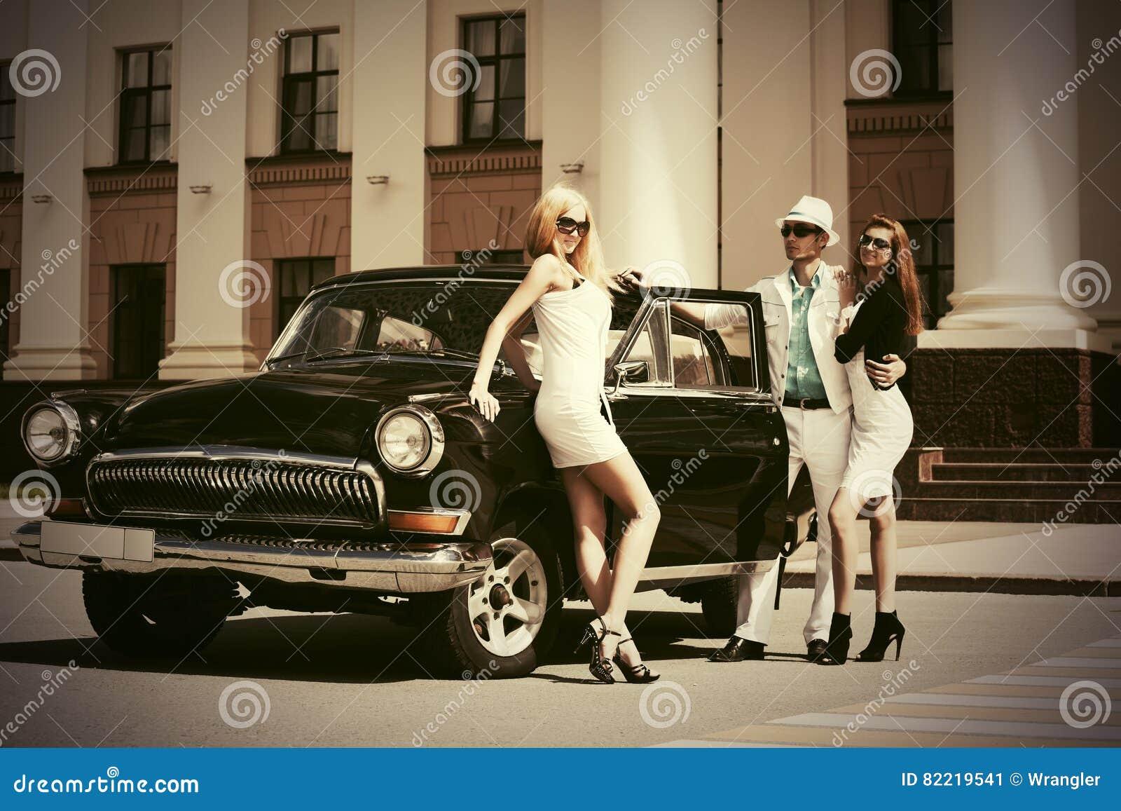 Giovani felici di modo accanto all automobile d annata