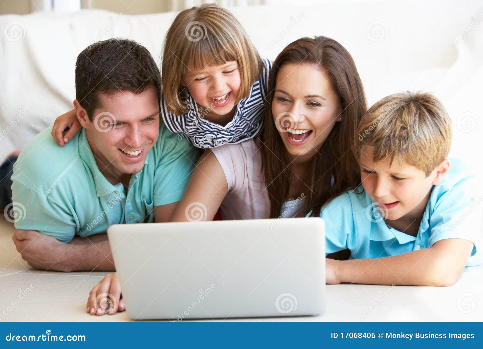 Giovani genitori, con i bambini, sul computer portatile