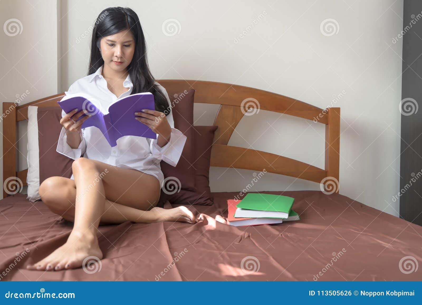 Giovani libri di lettura asiatici della donna sul letto di mattina che ritiene l ha