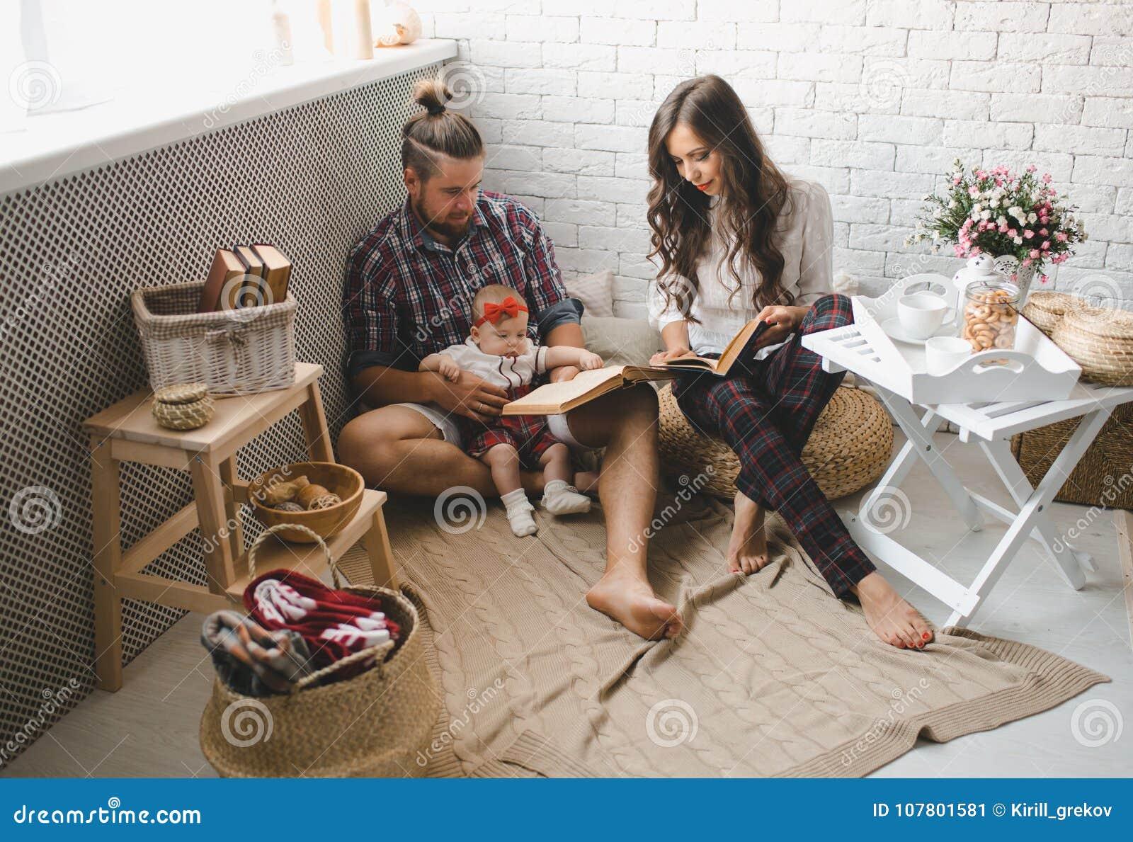 Giovani madre, padre felice e figlia della famiglia giocanti sul tappeto a casa