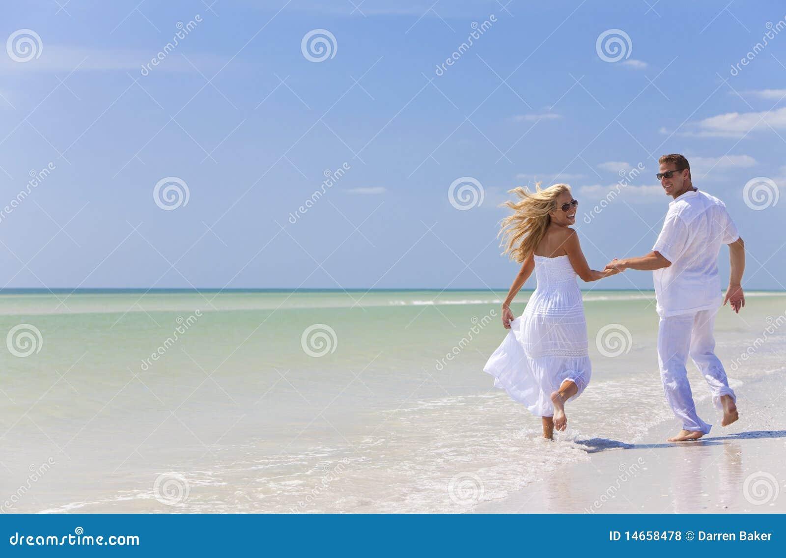 Giovani mani della holding delle coppie su una spiaggia tropicale