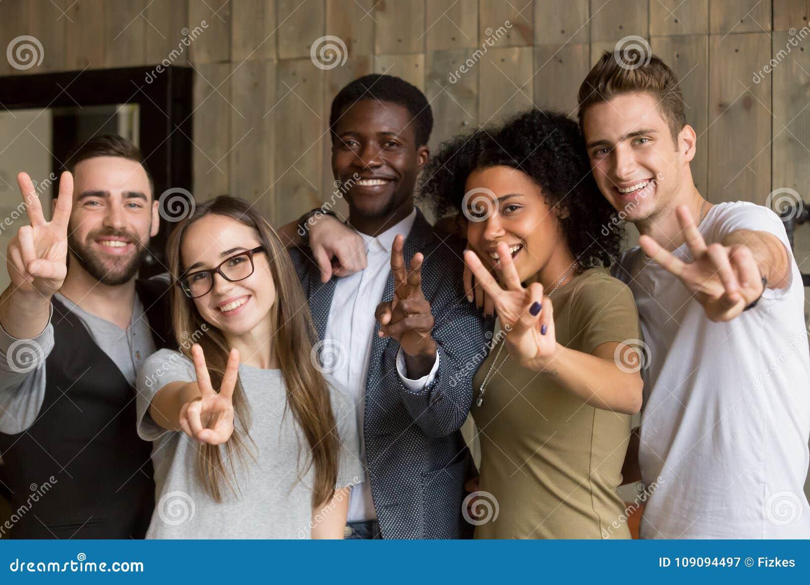 Giovani multi-etnici felici che mostrano il segno di pace che esamina Ca