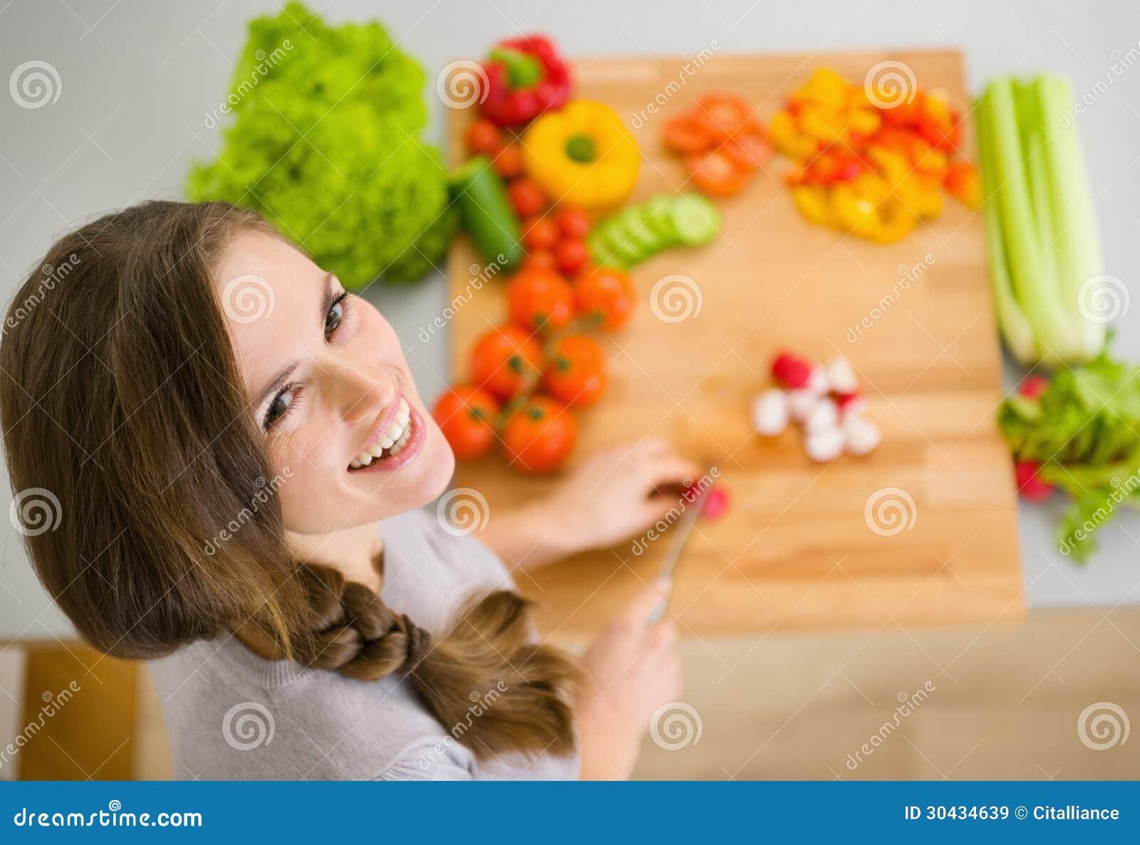 Giovani ortaggi freschi felici di taglio della casalinga