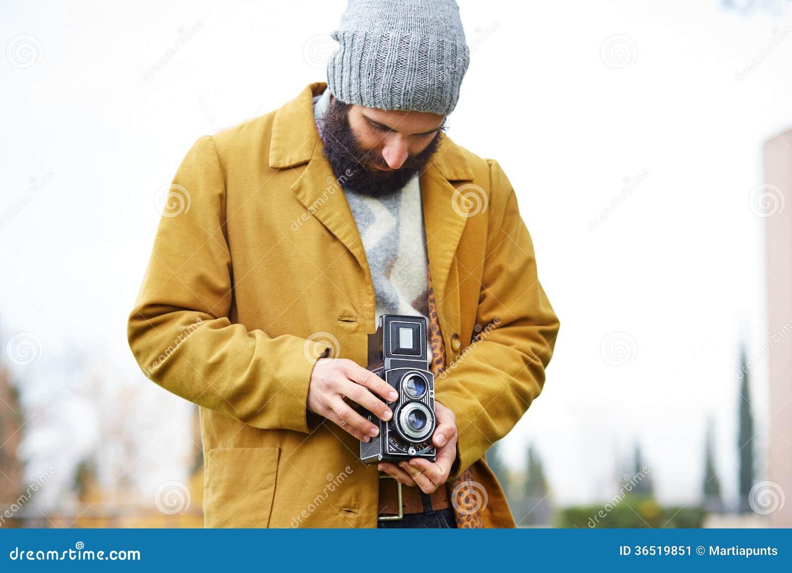 Giovani pantaloni a vita bassa barbuti che prendono foto con la macchina fotografica di TLR