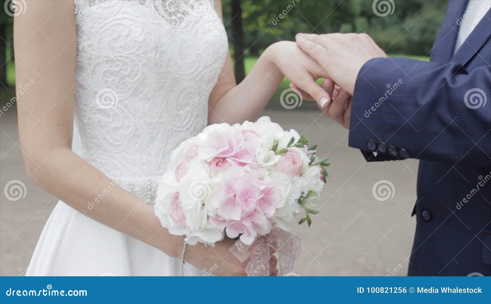 Giovani persone appena sposate che camminano fuori La sposa e lo sposo camminano insieme nel parco nell inverno o l estate e tene