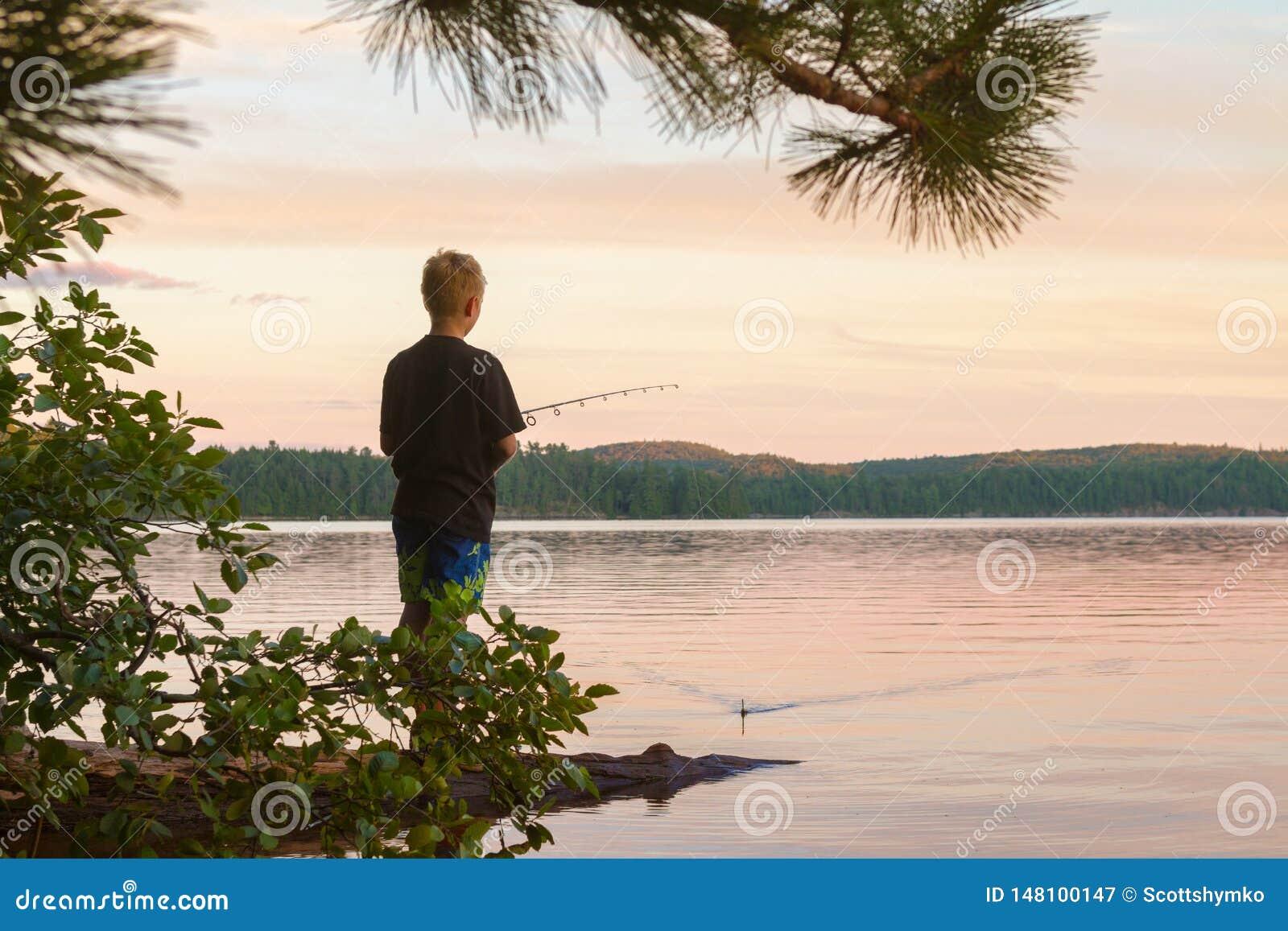 Giovani pesci del ragazzo in un lago al tramonto
