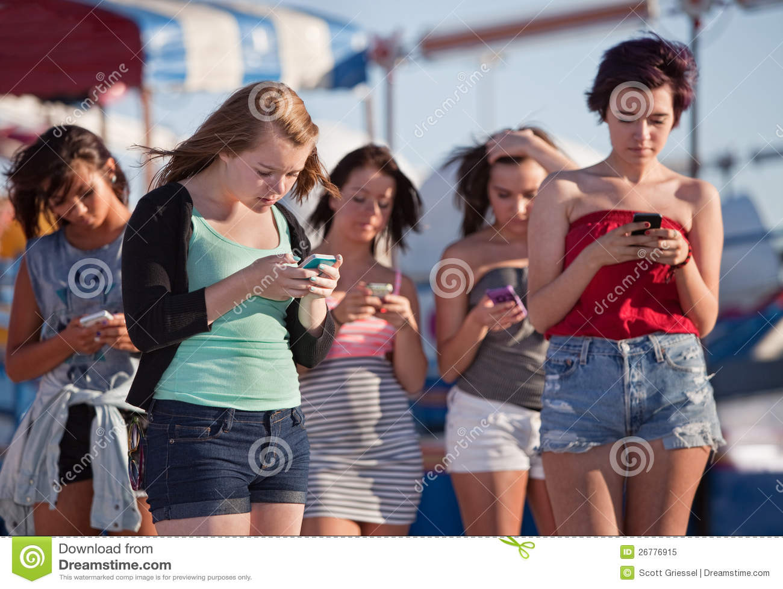 Giovani signore che per mezzo dei loro telefoni