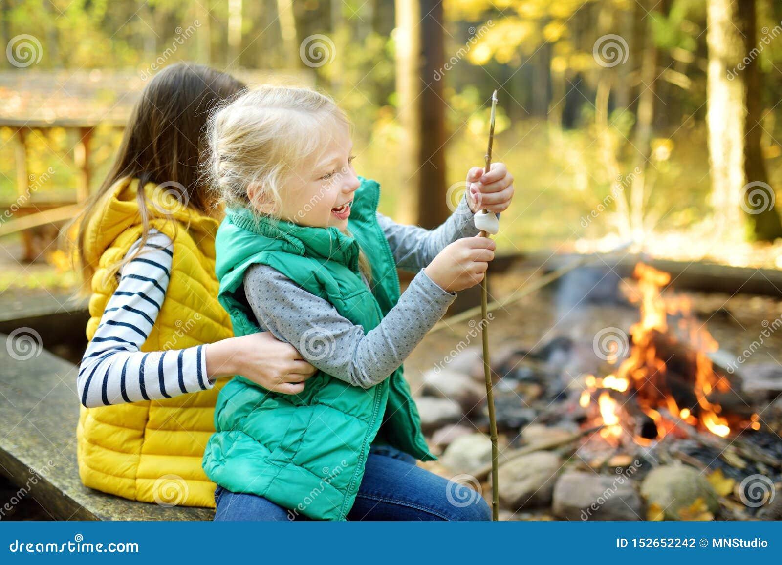 Giovani sorelle sveglie che arrostiscono le caramelle gommosa e molle sul bastone al falò Bambini divertendosi al fuoco del campo
