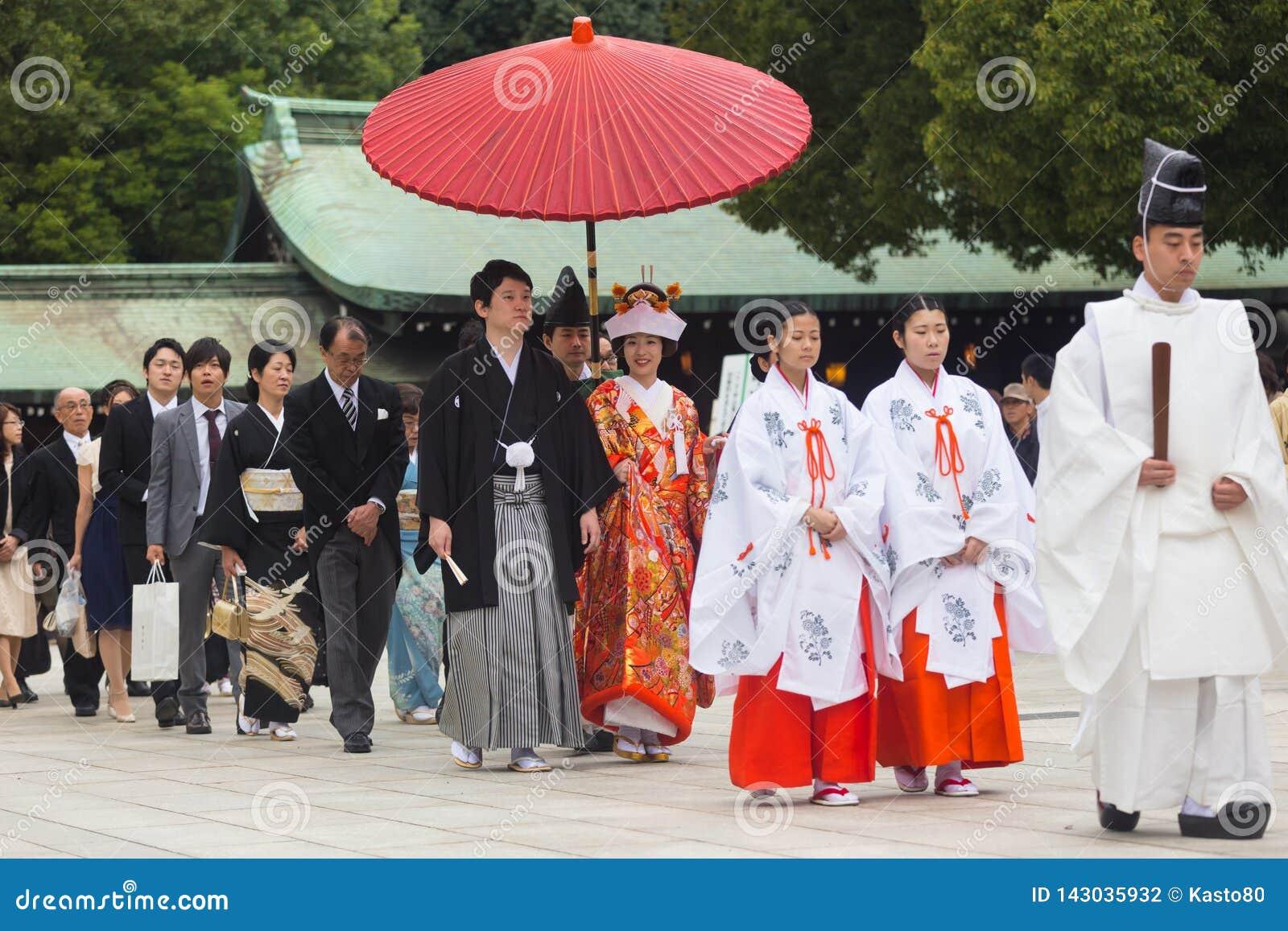 Giovani sposo e sposa felici durante la cerimonia di nozze tradizionale giapponese al santuario di Meiji-jingu a Tokyo, Giappone