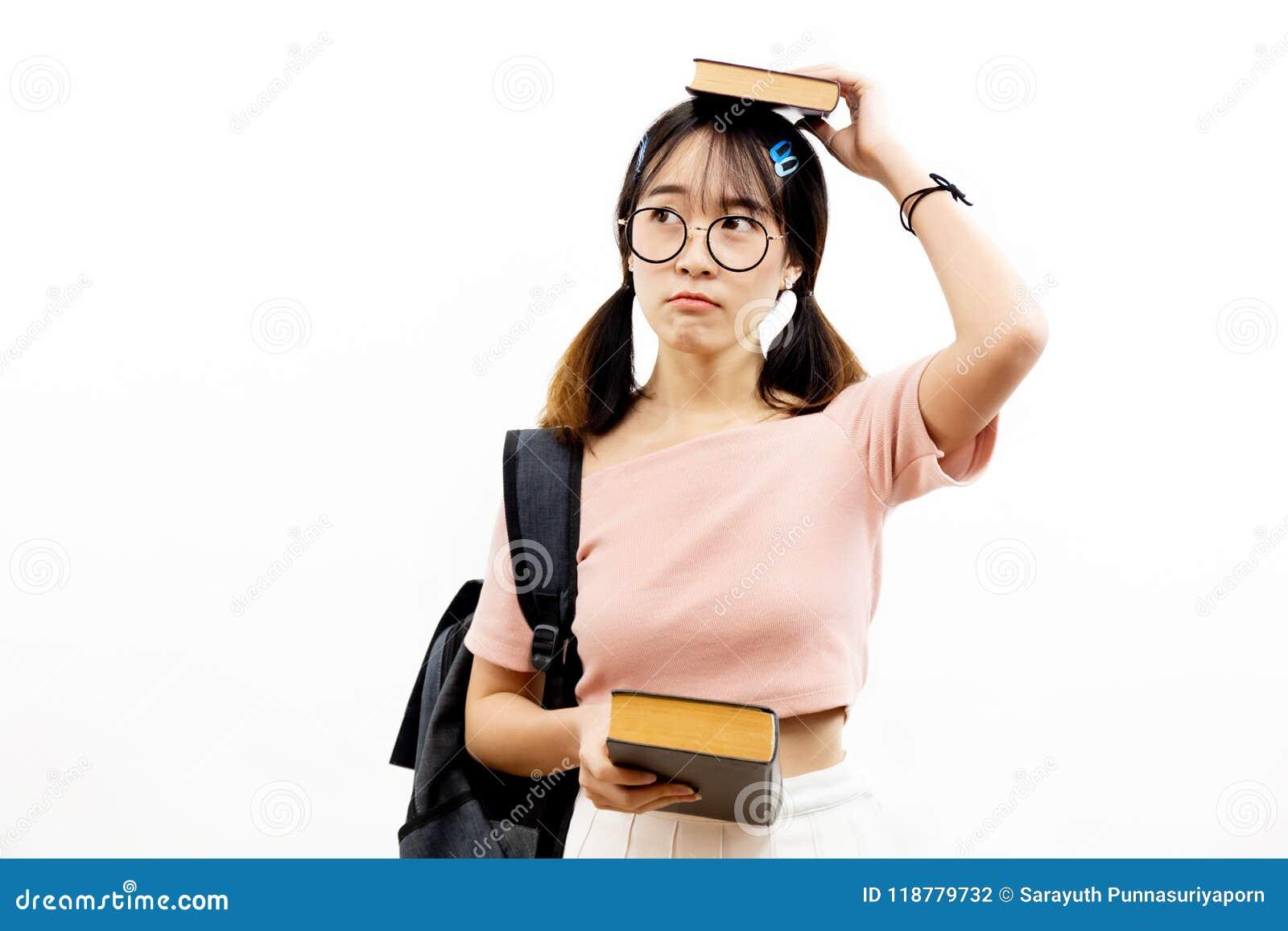 Giovani studenti teenager accademici femminili asiatici con i vetri d avanguardia dell occhio che tengono mucchio dei libri con l
