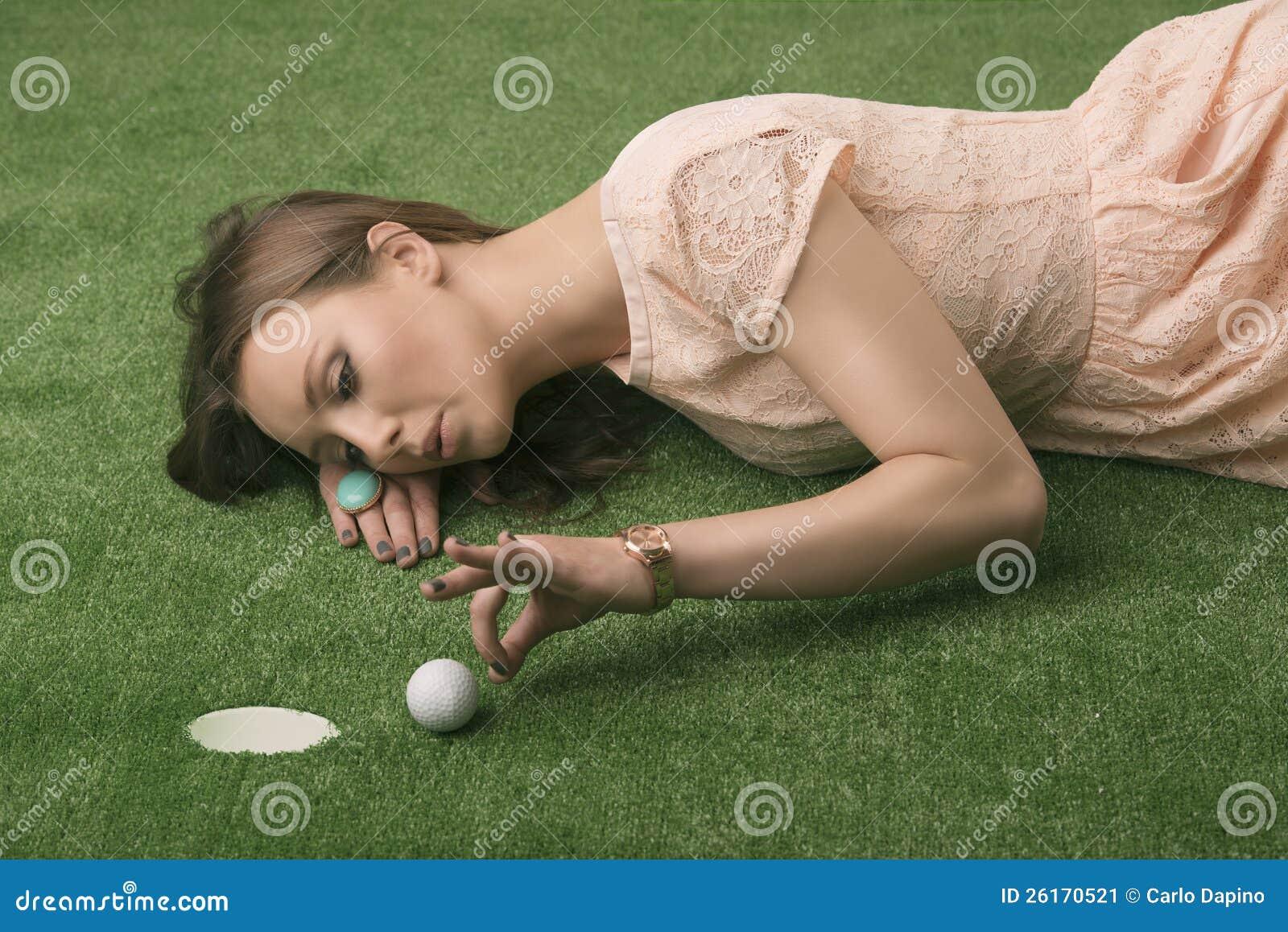 Girlâs se trouvant sur l herbe avec la bille de golf