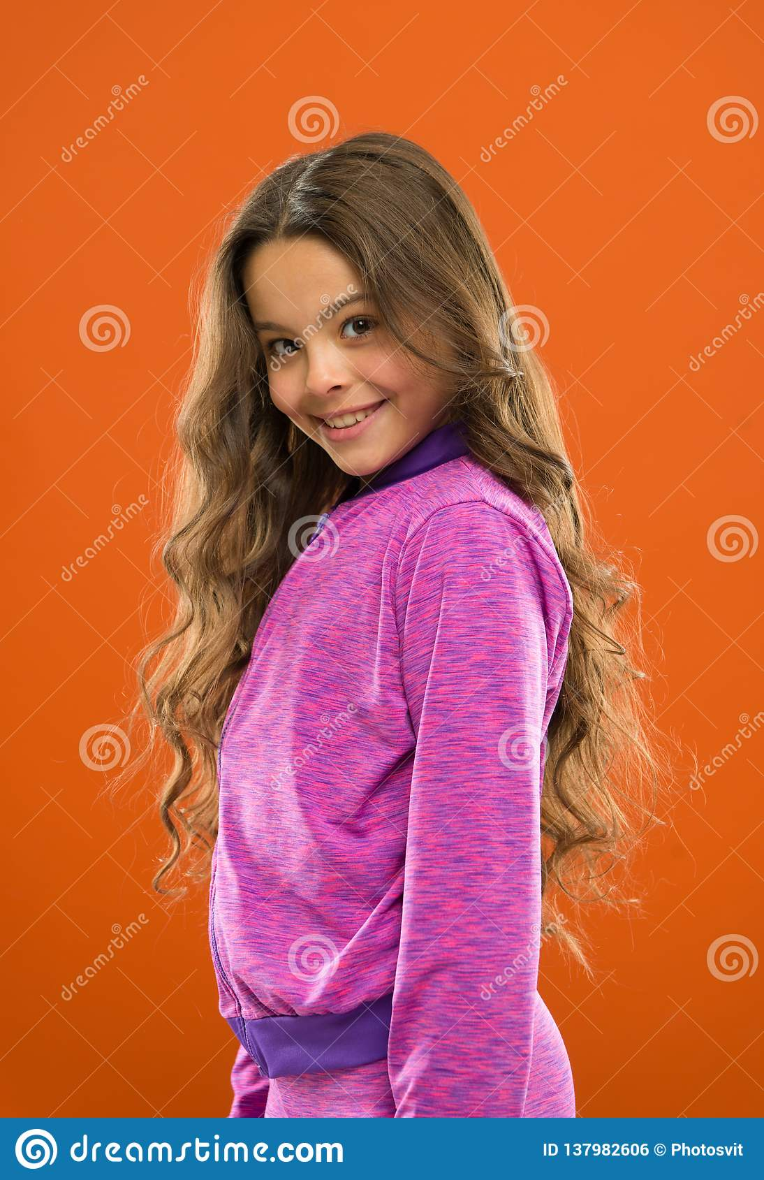 Girl active kid with long gorgeous hair. Strong and healthy hair concept. How to treat curly hair. Nice and tidy