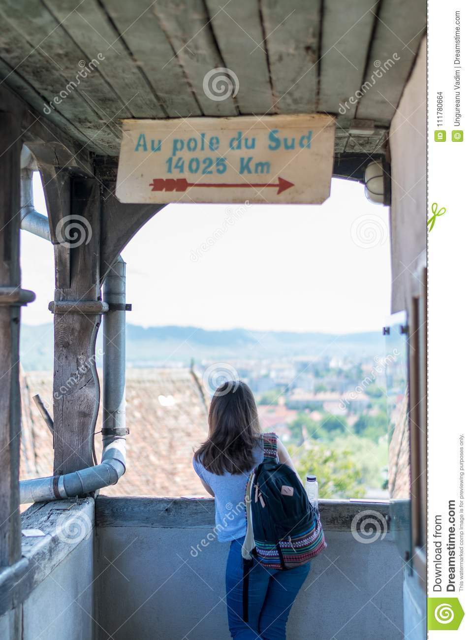 A girl admiring the view from Sighisoara Clock Tower on a sunny day.