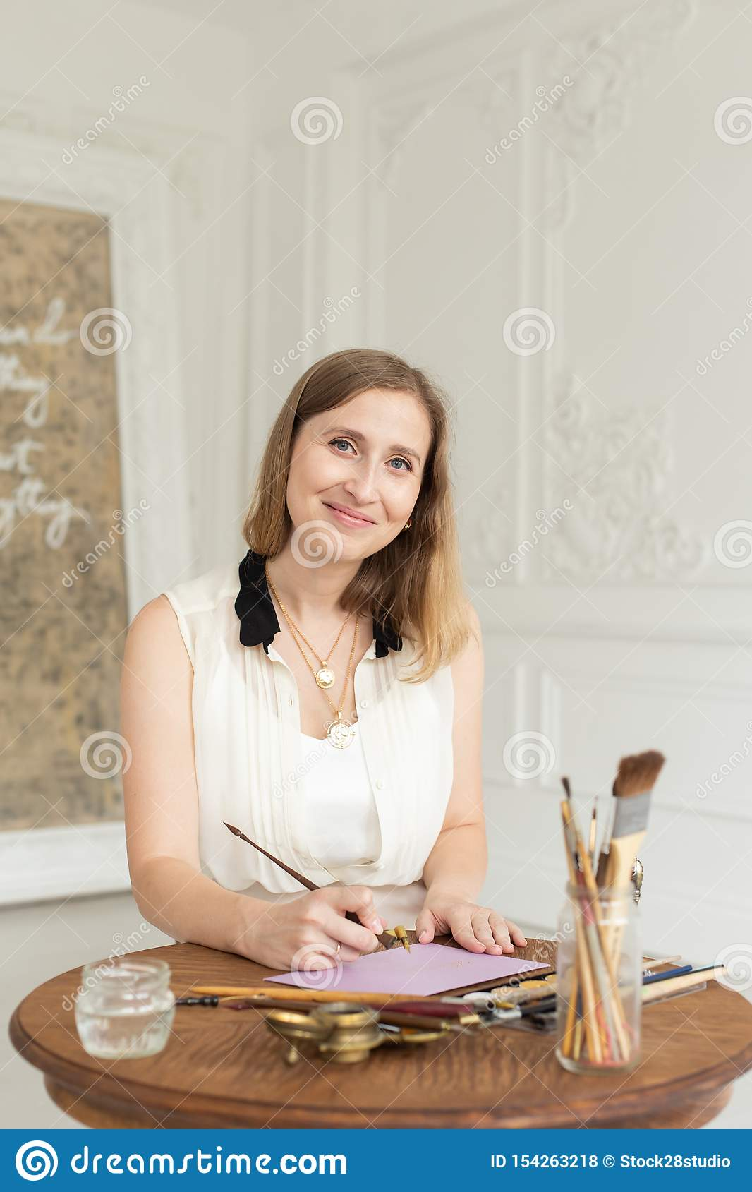 The girl artist is inspired and paints a picture. Holds a brush. Soft focus. Interior artist`s workshop.