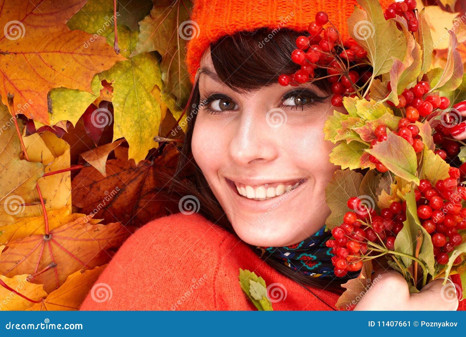 Girl in autumn orange hat on leaf group.