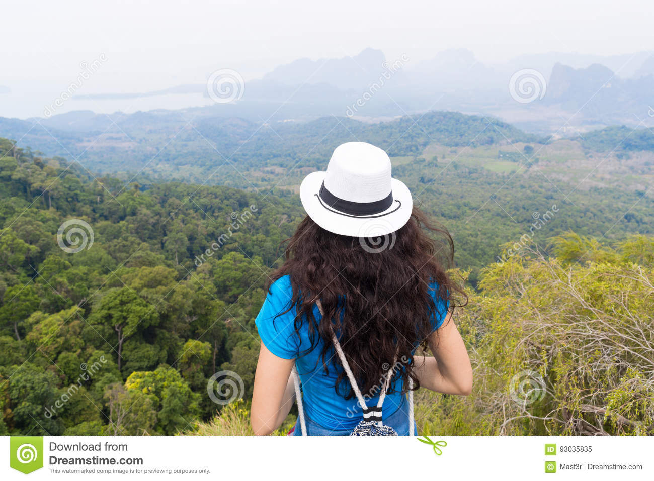 Girl standing on rocky ledge overlooking river with her