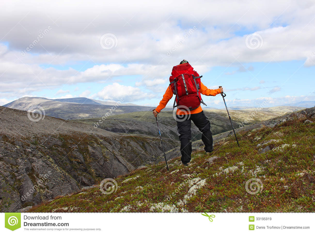 Girl with backpack standing on top of a mountain and looking at the    Girl Standing On Top Of A Mountain