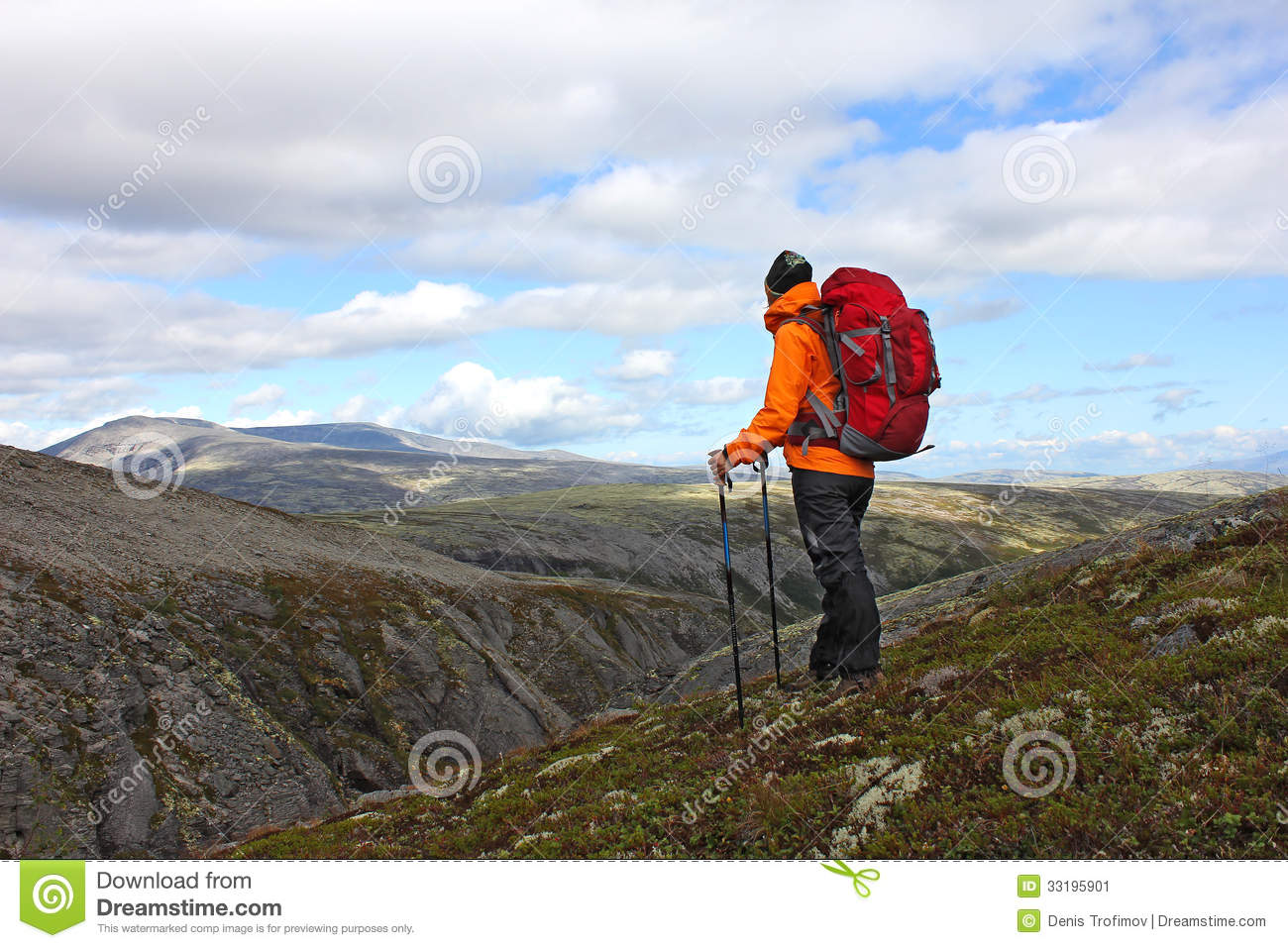 Girl with backpack standing on top of a mountain and looking for way    Girl Standing On Top Of A Mountain