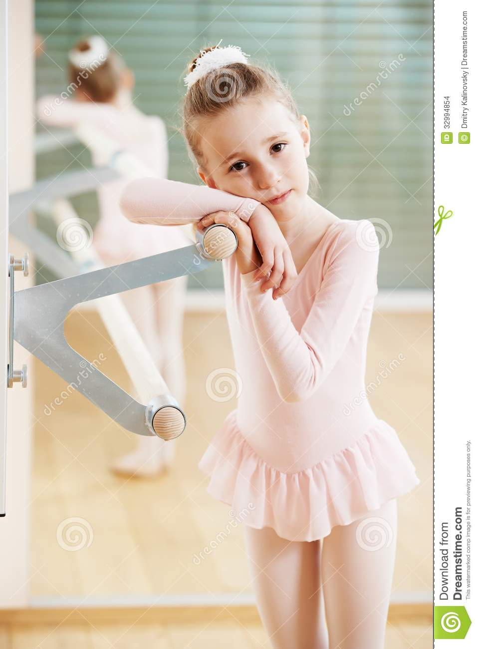 Little girl in ballet suit at training exercise in front of mirror.