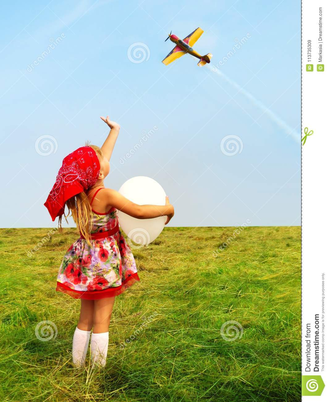 Girl with a balloon waving a hand flying aircraft.