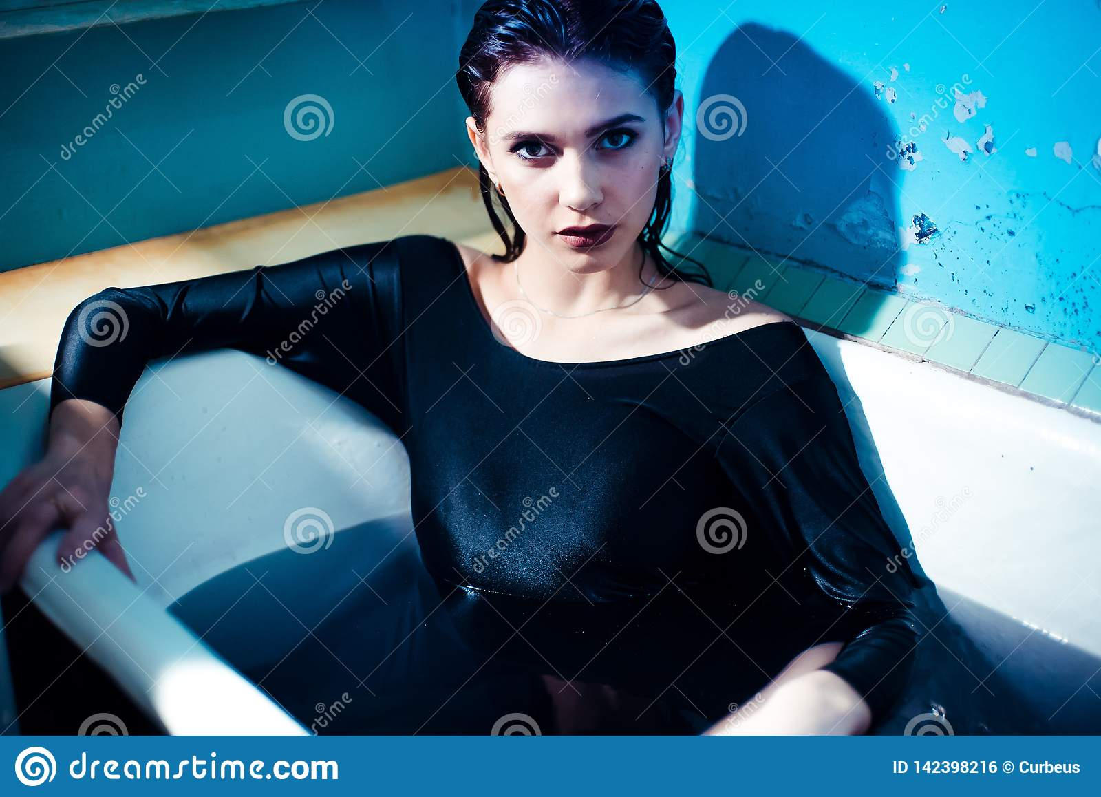 Girl with bare shoulders lying in the bathroom with colored purple water. Fashion concept