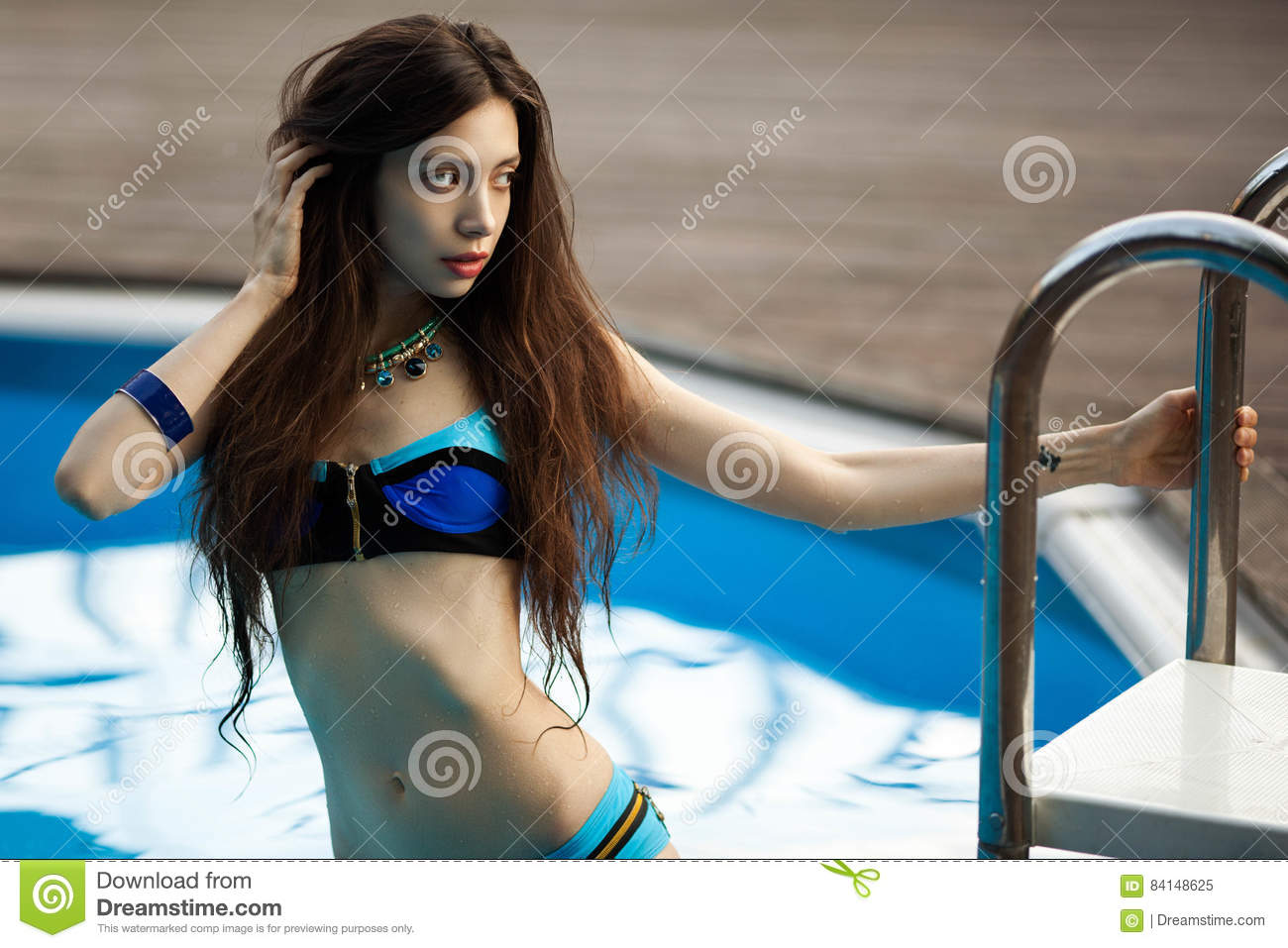 Girl in a bathing suit on the background of the pool