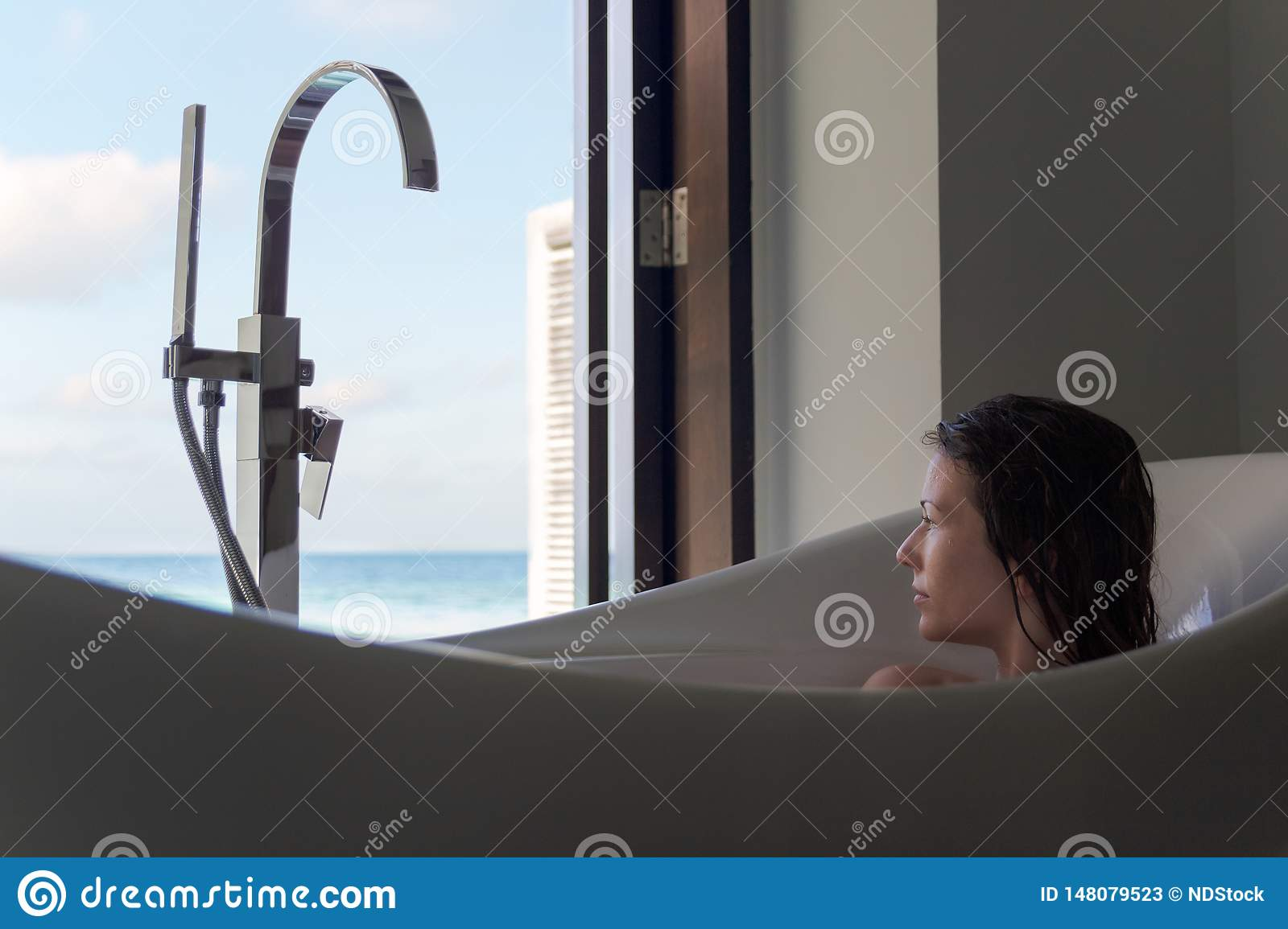 Young woman in bathtub admiring the view from the window. Tropical holiday destination