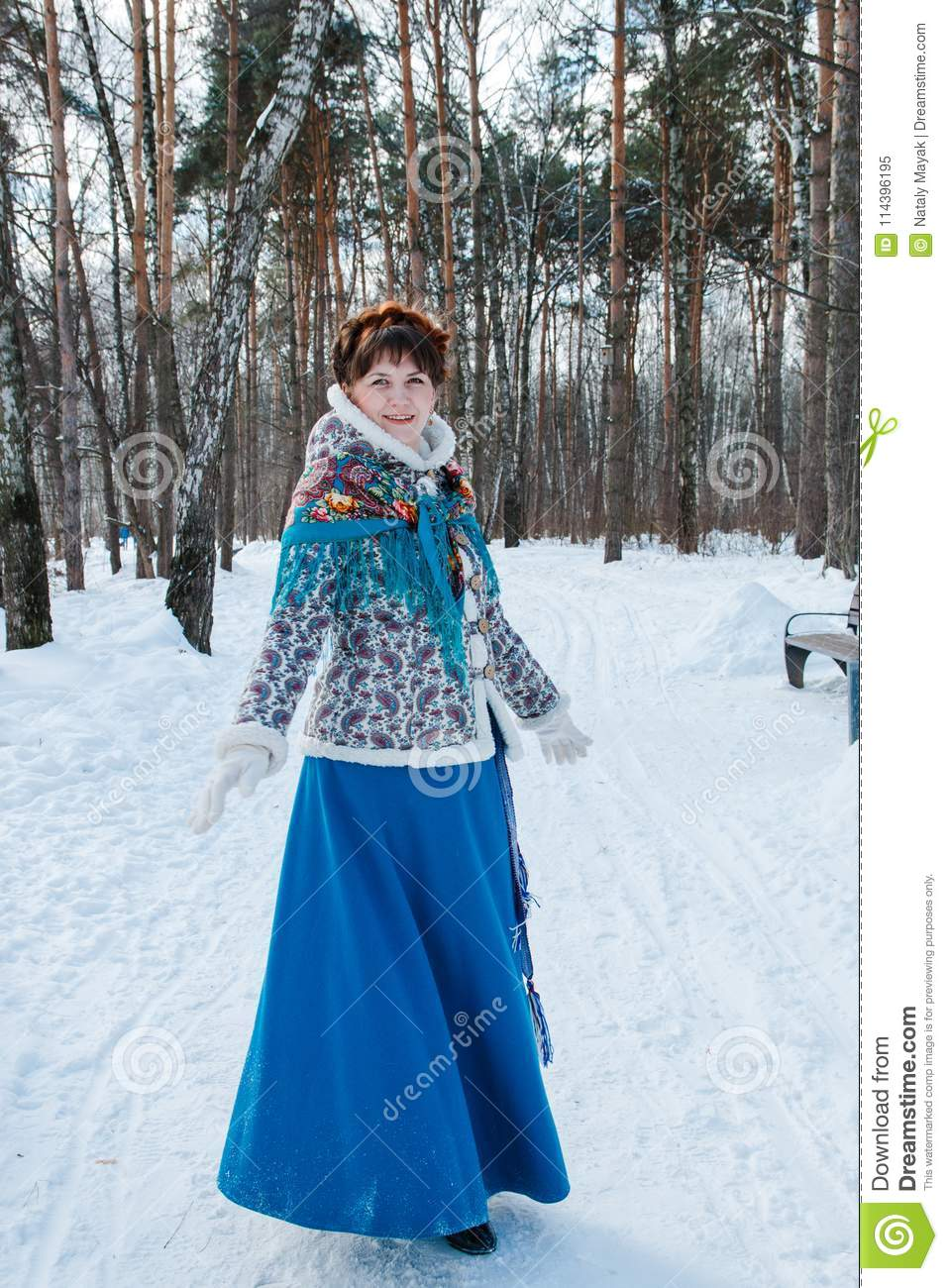 A girl with beautiful hair on her head in a Slavic style in full growth in the winter forest