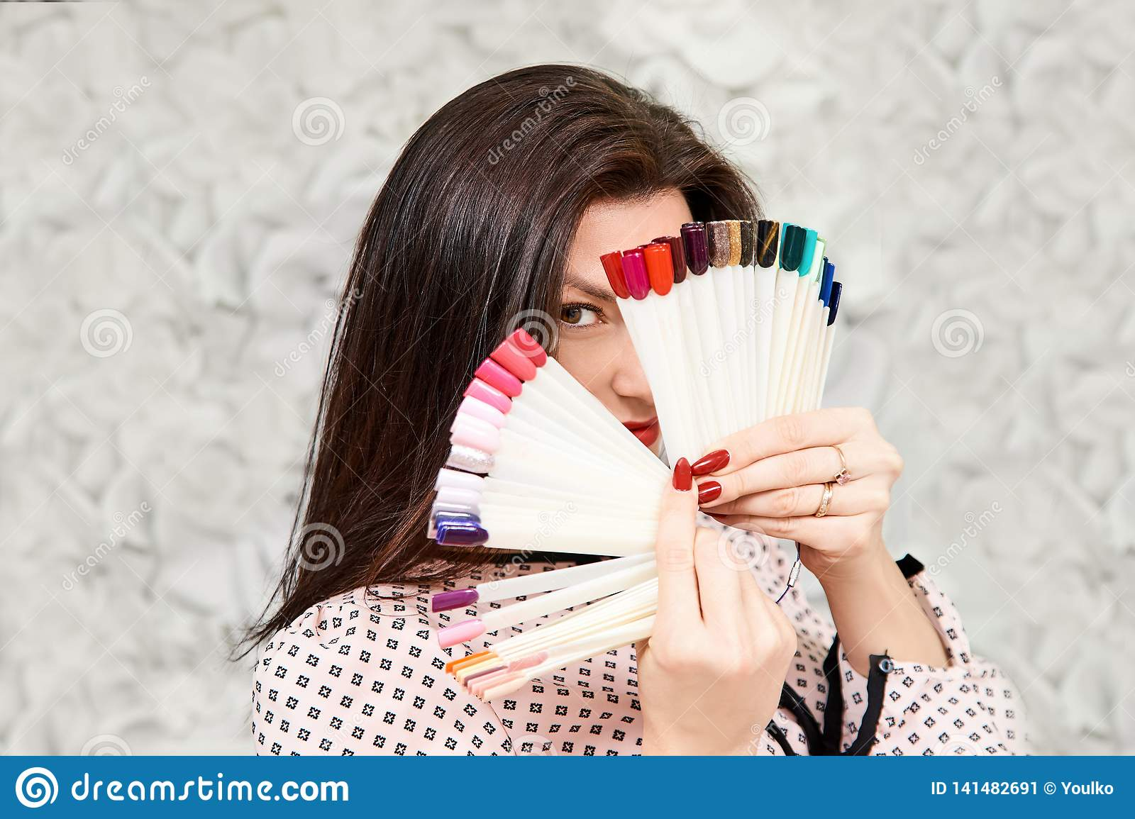 A girl with a beautiful manicure, holding manicure samples, covering her face. Brunette