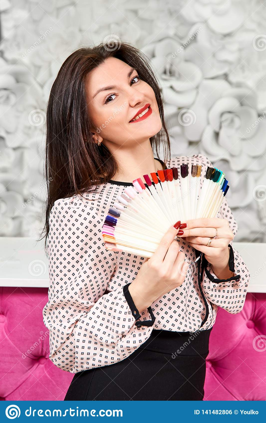 A girl with a beautiful manicure, holding samples of manicure and smiling. Brunette