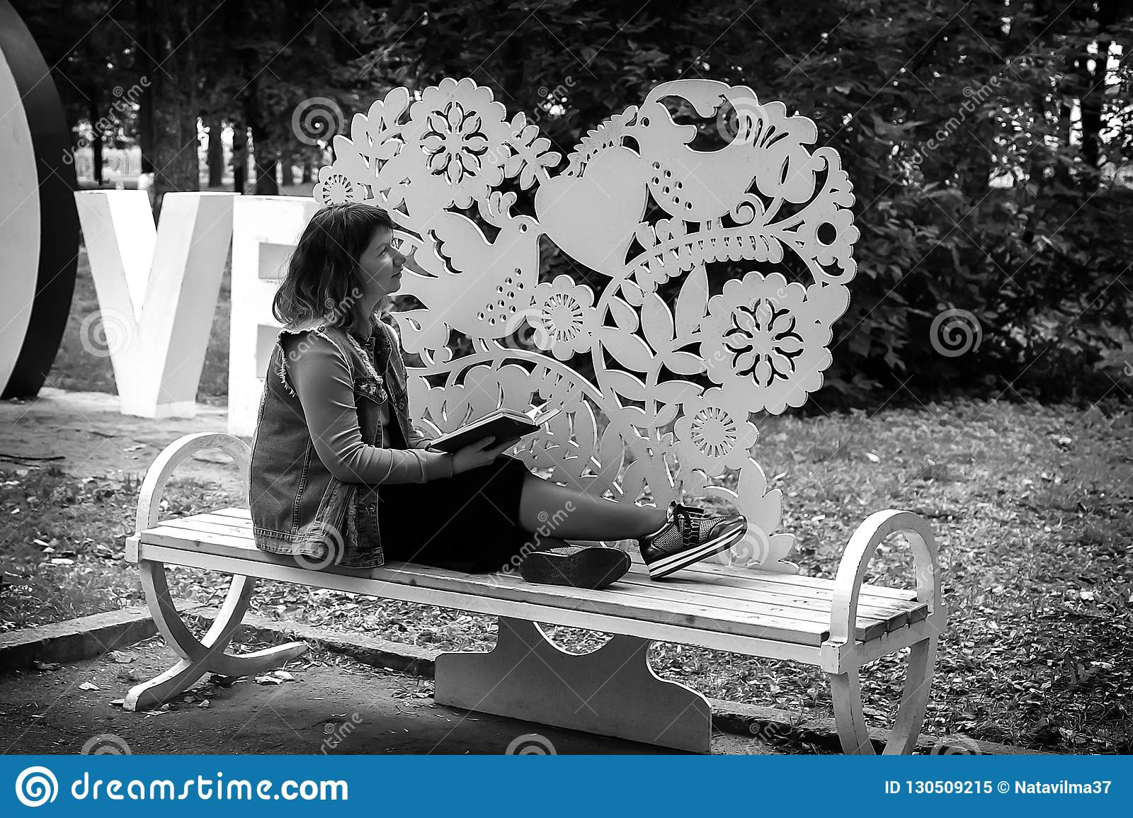 Girl on a bench in the Park with a book in her hands, black and white photo