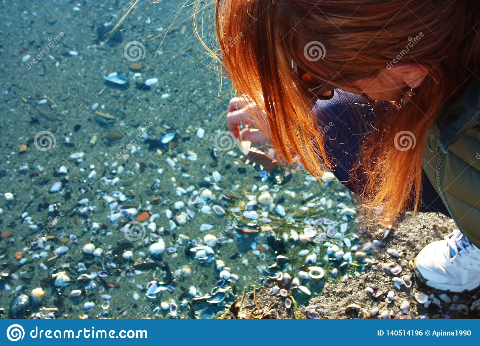 Girl bent over the beach collects shells in the sand