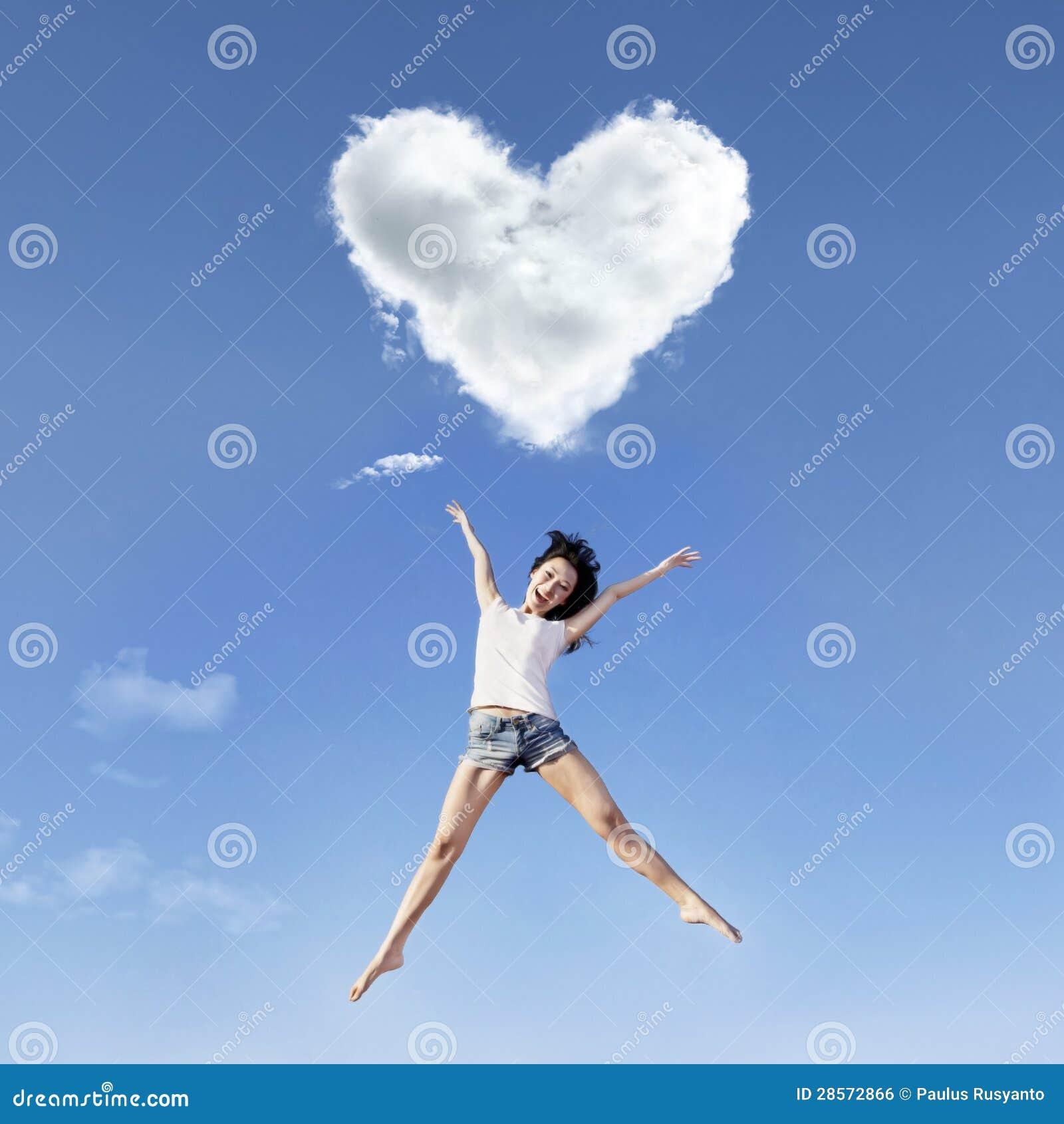 Girl big jump under heart clouds