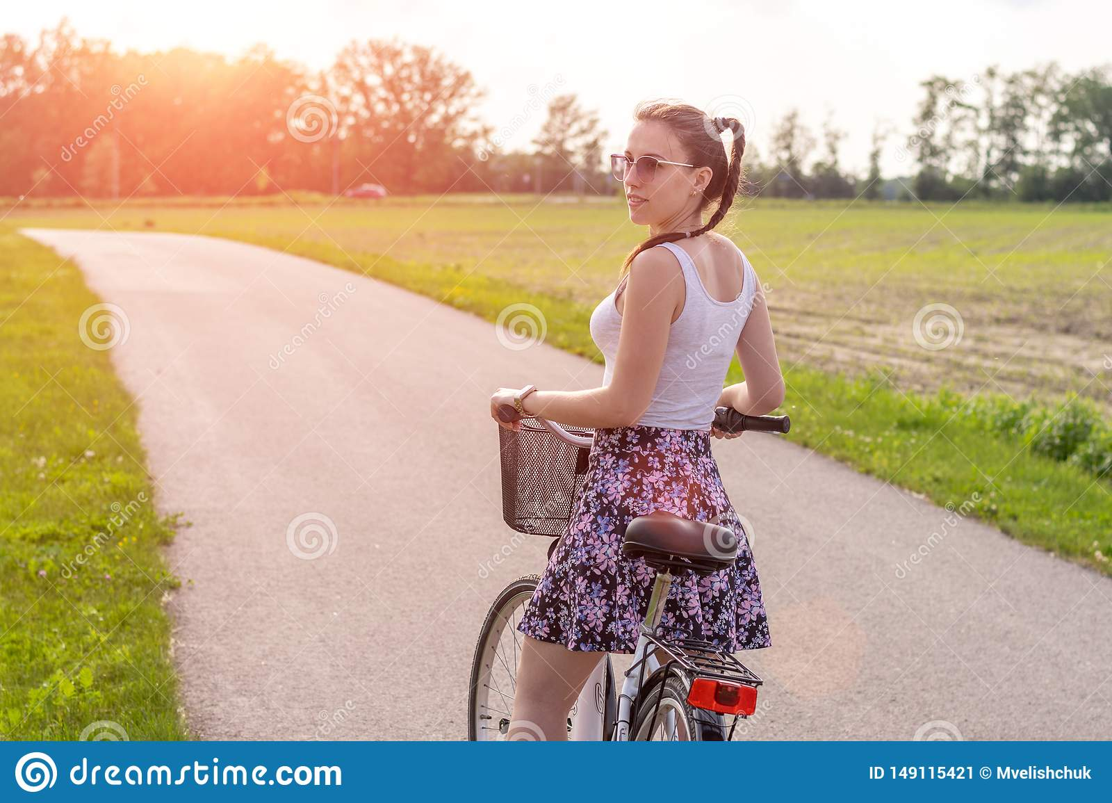 Girl with bike at the summer sunset on the road in the city park. Cycle closeup wheel on blurred summer background. Cycling down t