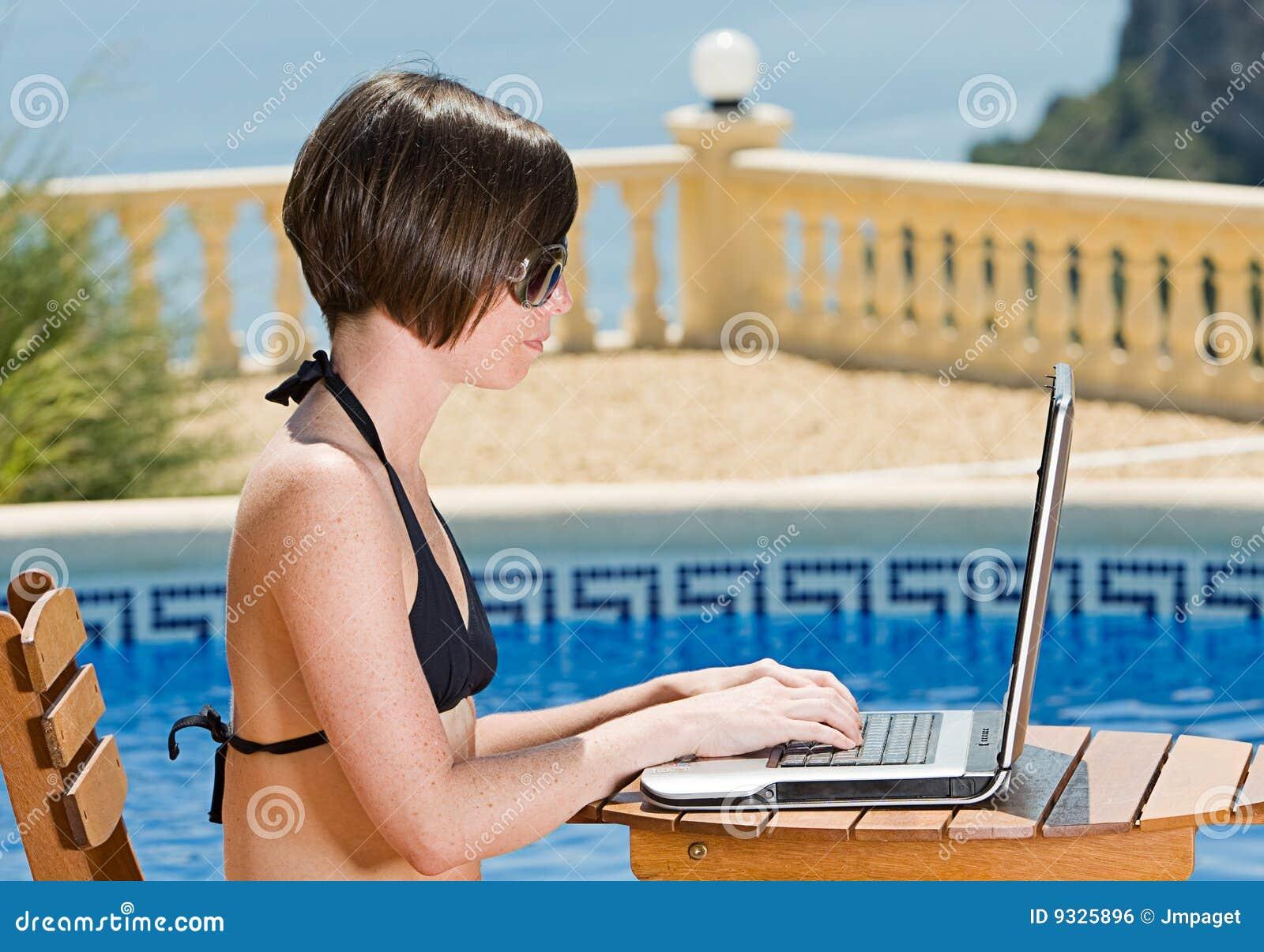 Girl In Bikini Using Laptop By The Pool