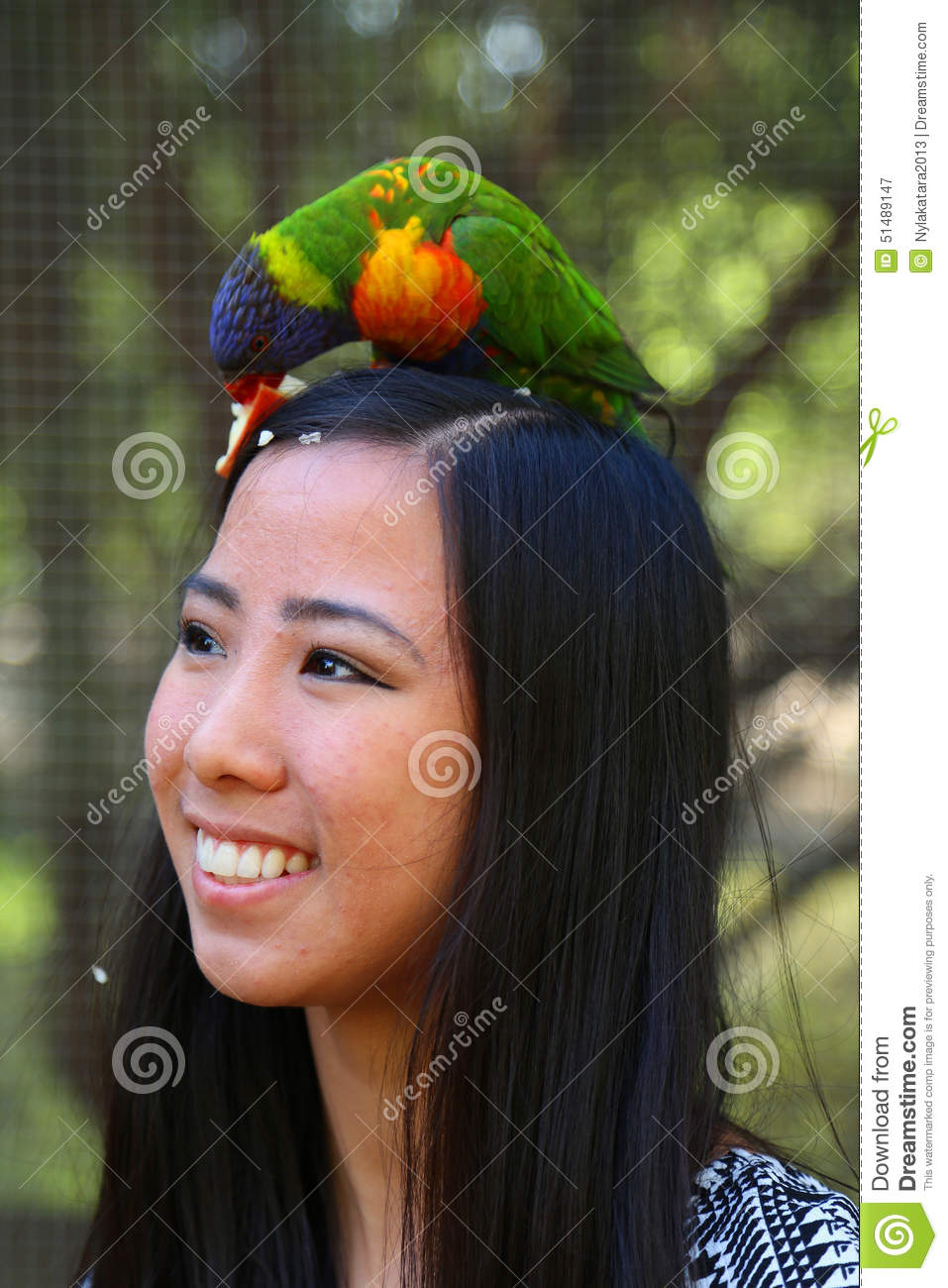 ... vibrant Lories also known as lorikeets on her head eating an apple
