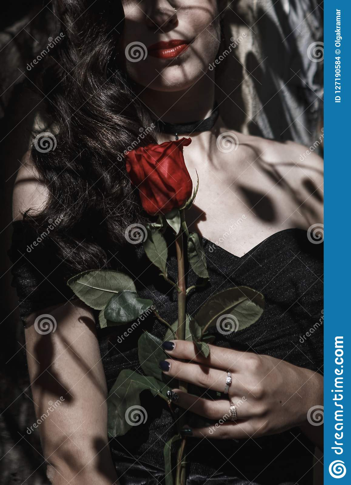 A girl in a black dress with red lips and a red rose. Black shadow patterns on the face.